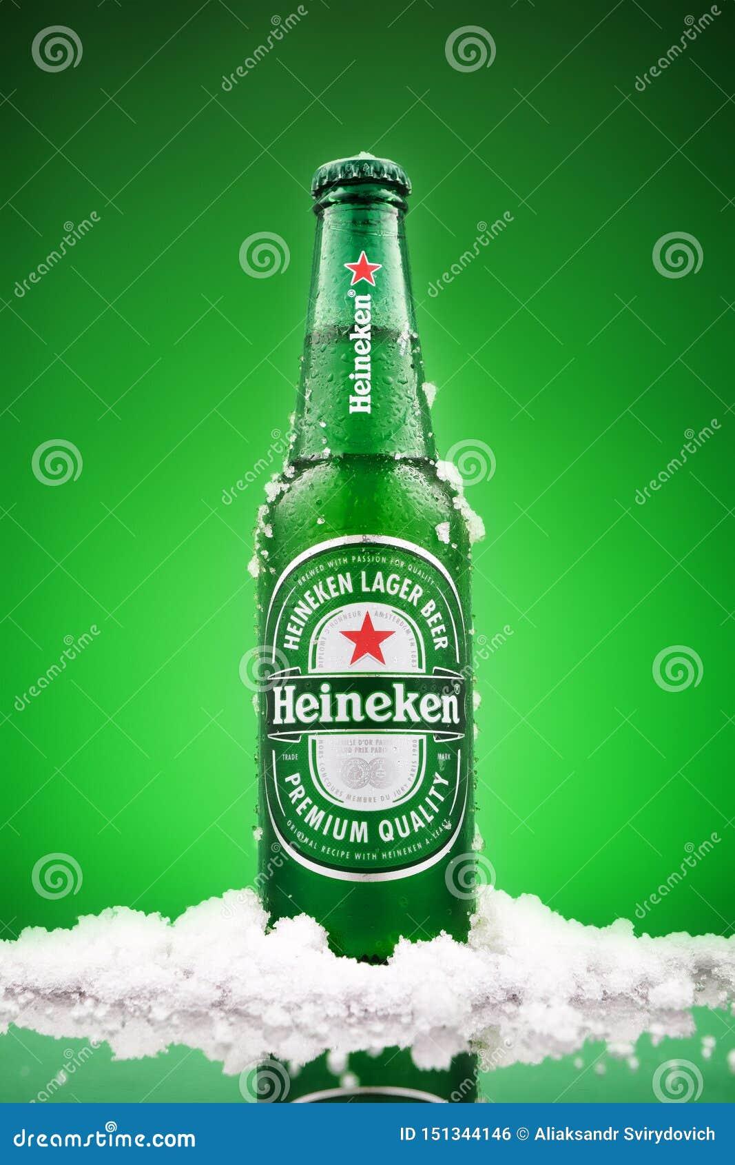 МИНСК, БЕЛАРУСЬ - 13-ОЕ МАРТА 2019: Холодная бутылка пива лагера Heineken над зеленой предпосылкой Heineken корабль- флагман
