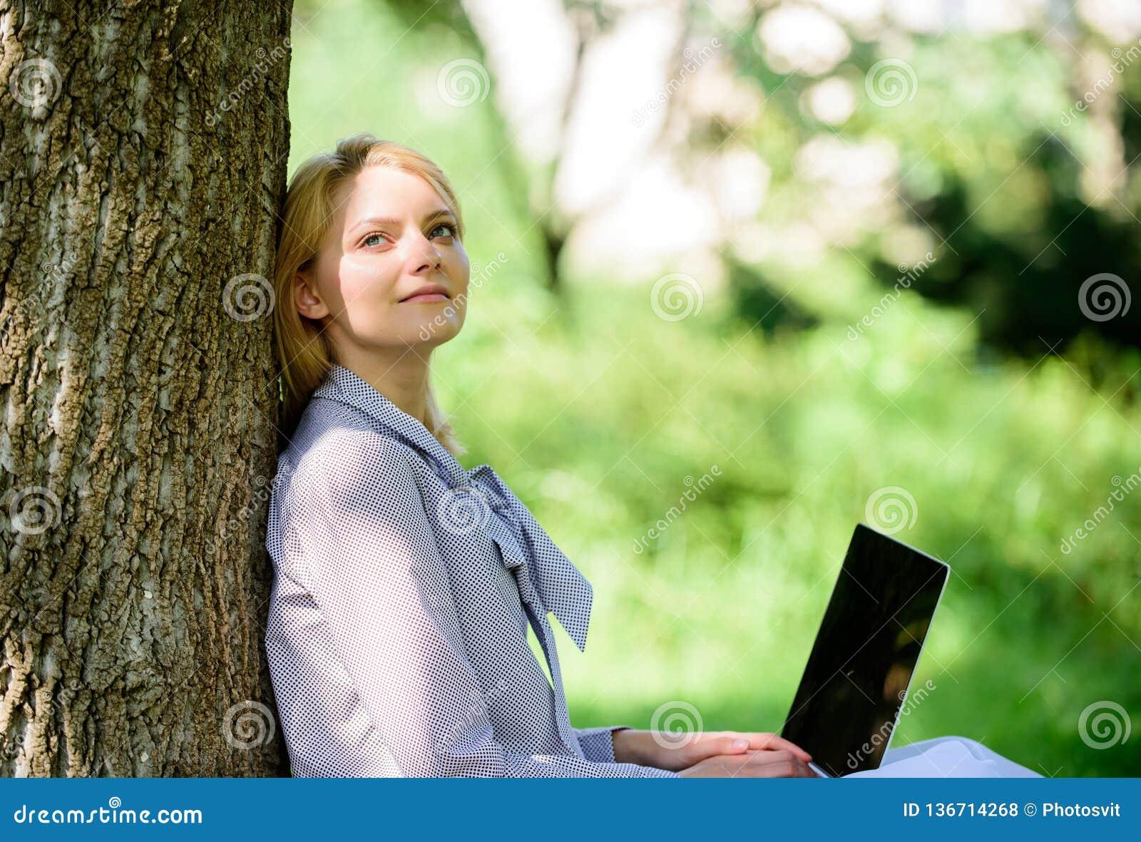 Минута для ослабляет Работа девушки с ноутбуком в парке сидеть на траве Технология образования и концепция интернета естественно