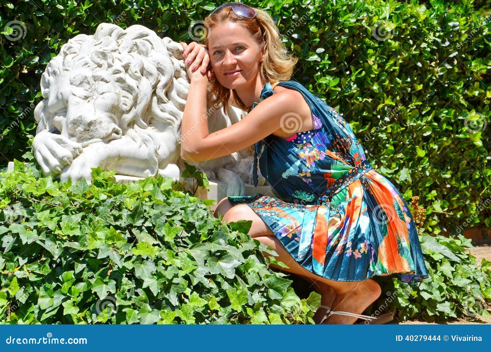 Милая девушка в платье лета около статуи льва, концепции летних каникулов