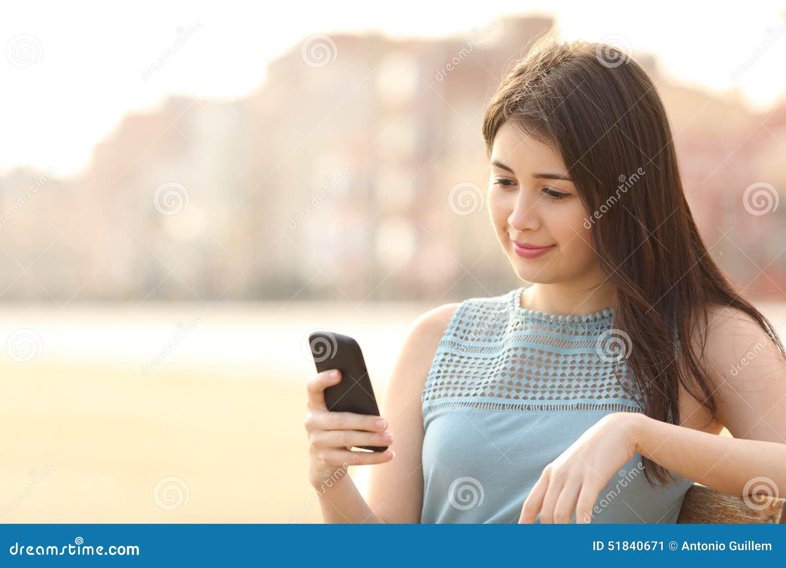 Милая девушка используя мобильный телефон в городском парке