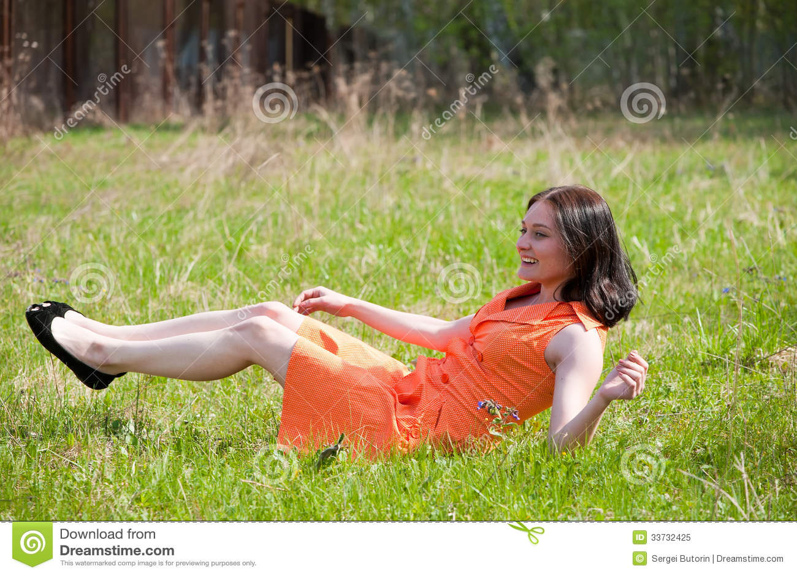 Милая девушка кладя на траву