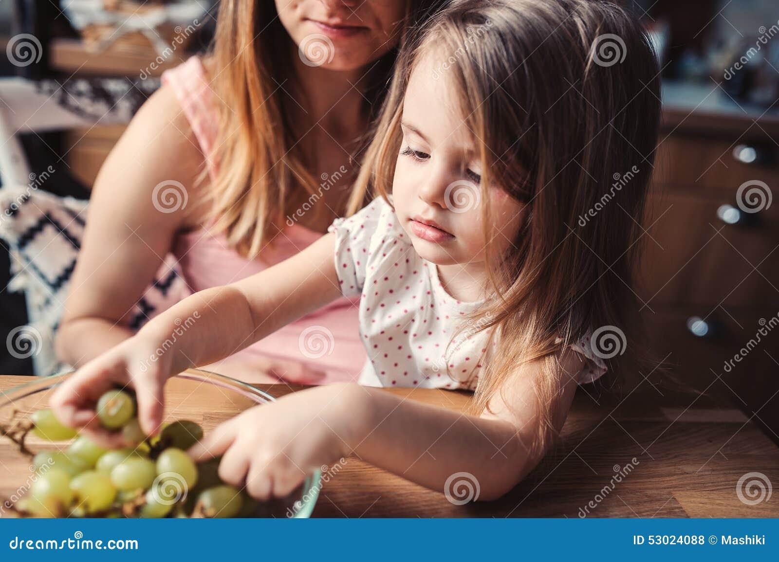 Милая девушка малыша есть виноградины с матерью на кухне