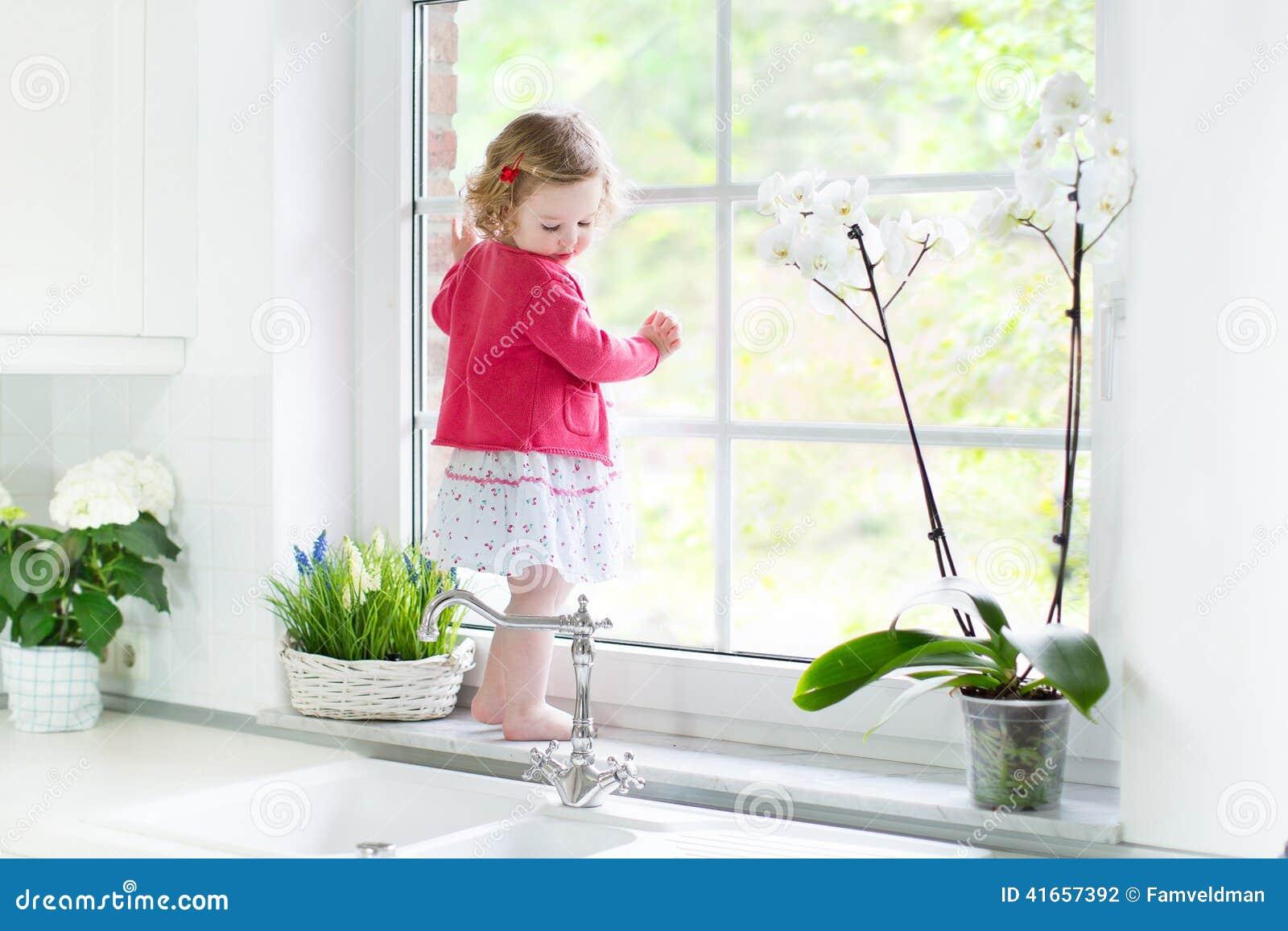 Милая девушка малыша наблюдая вне окно в белой кухне