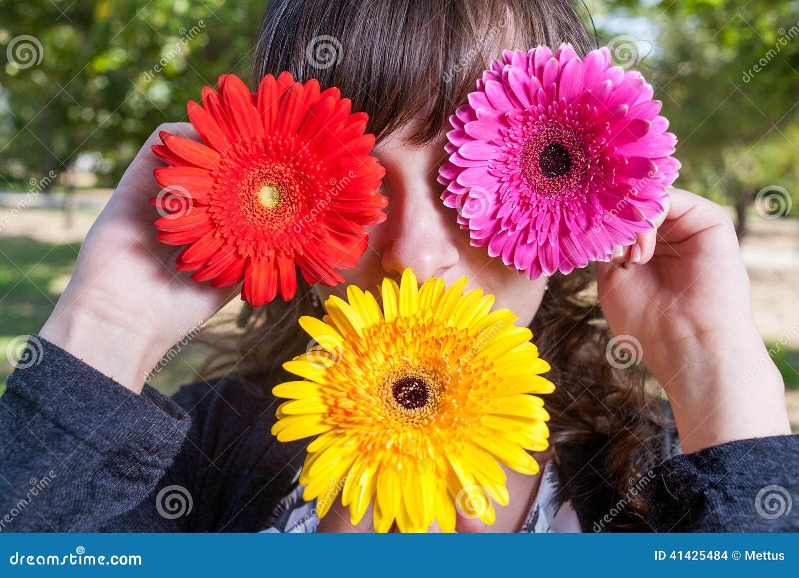 Милая девушка прячет ее глаза и рот цветками gerbera