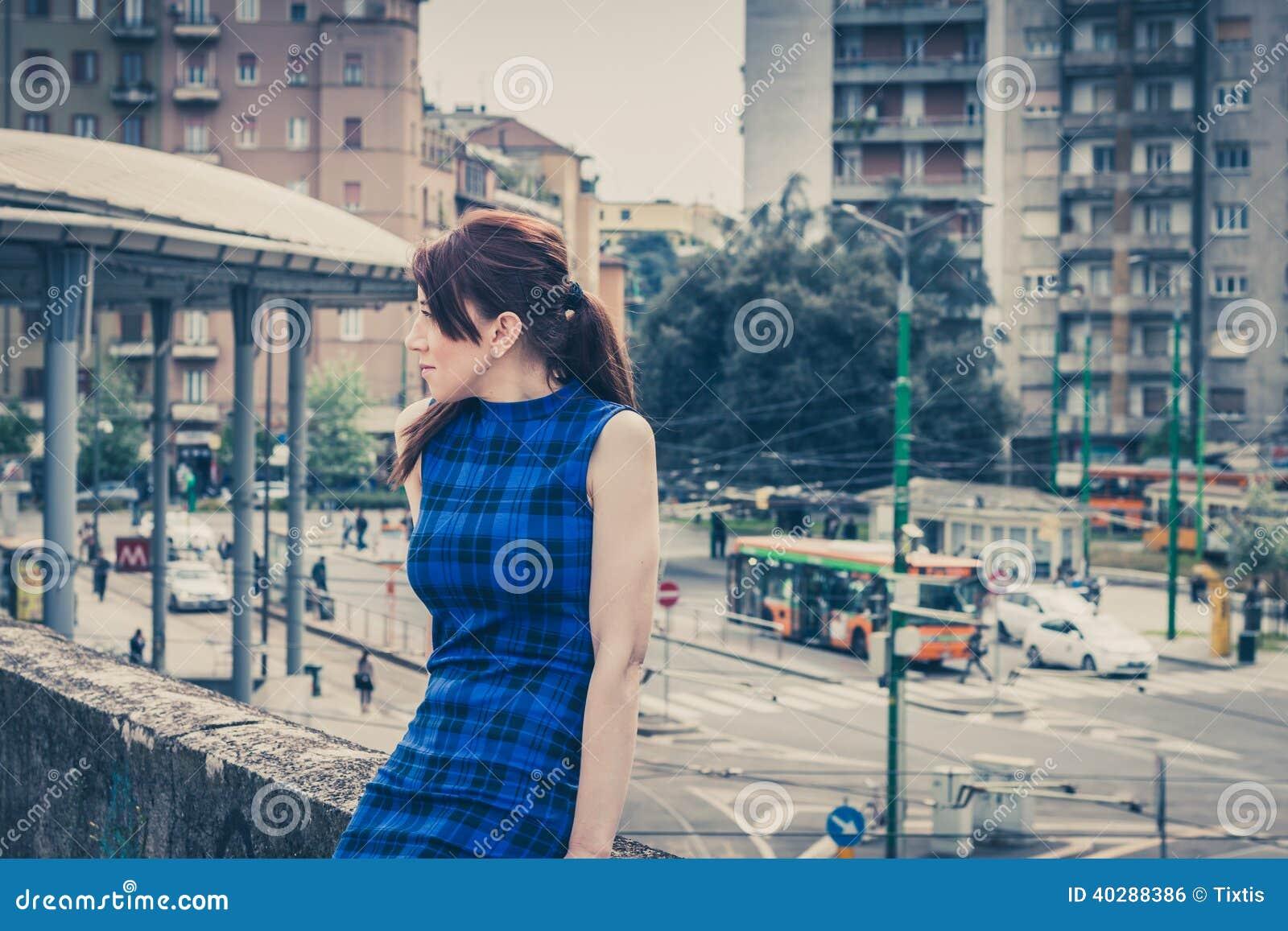 Милая девушка сидя на бетонной стене