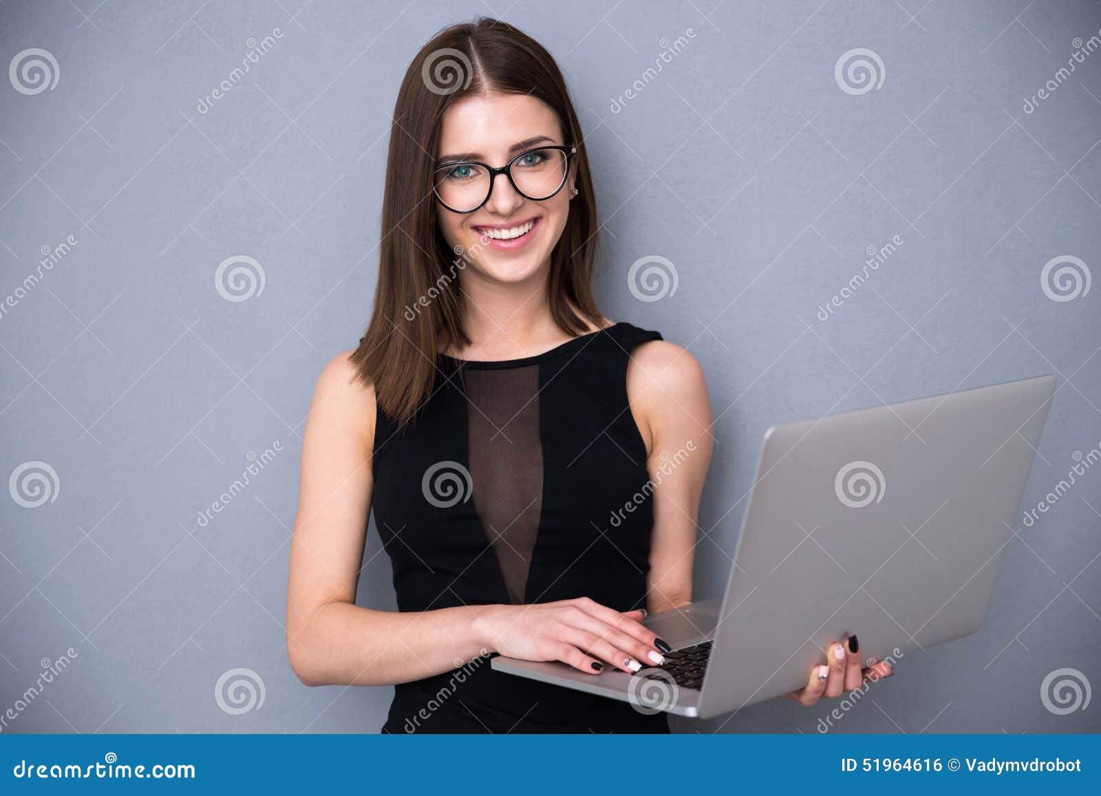 Милая женщина при компьтер-книжка стоя над серой предпосылкой