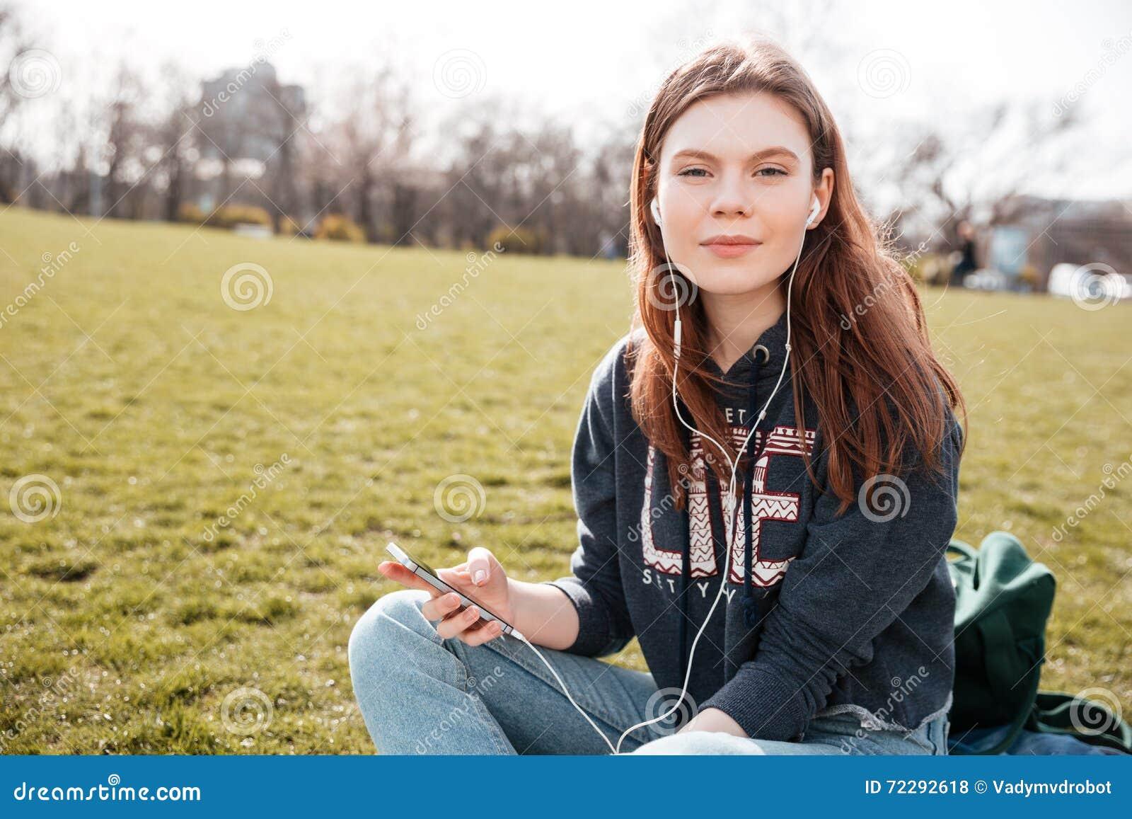 Download Милая женщина слушая к музыке от мобильного телефона на лужайке Стоковое Фото - изображение насчитывающей повелительница, клетка: 72292618