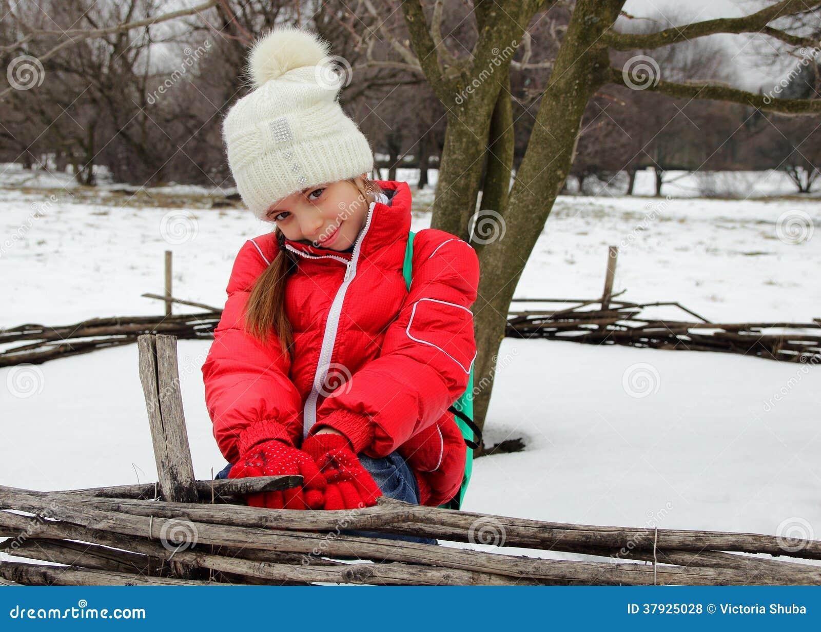 Милая маленькая девочка в крышке и куртке усмехается