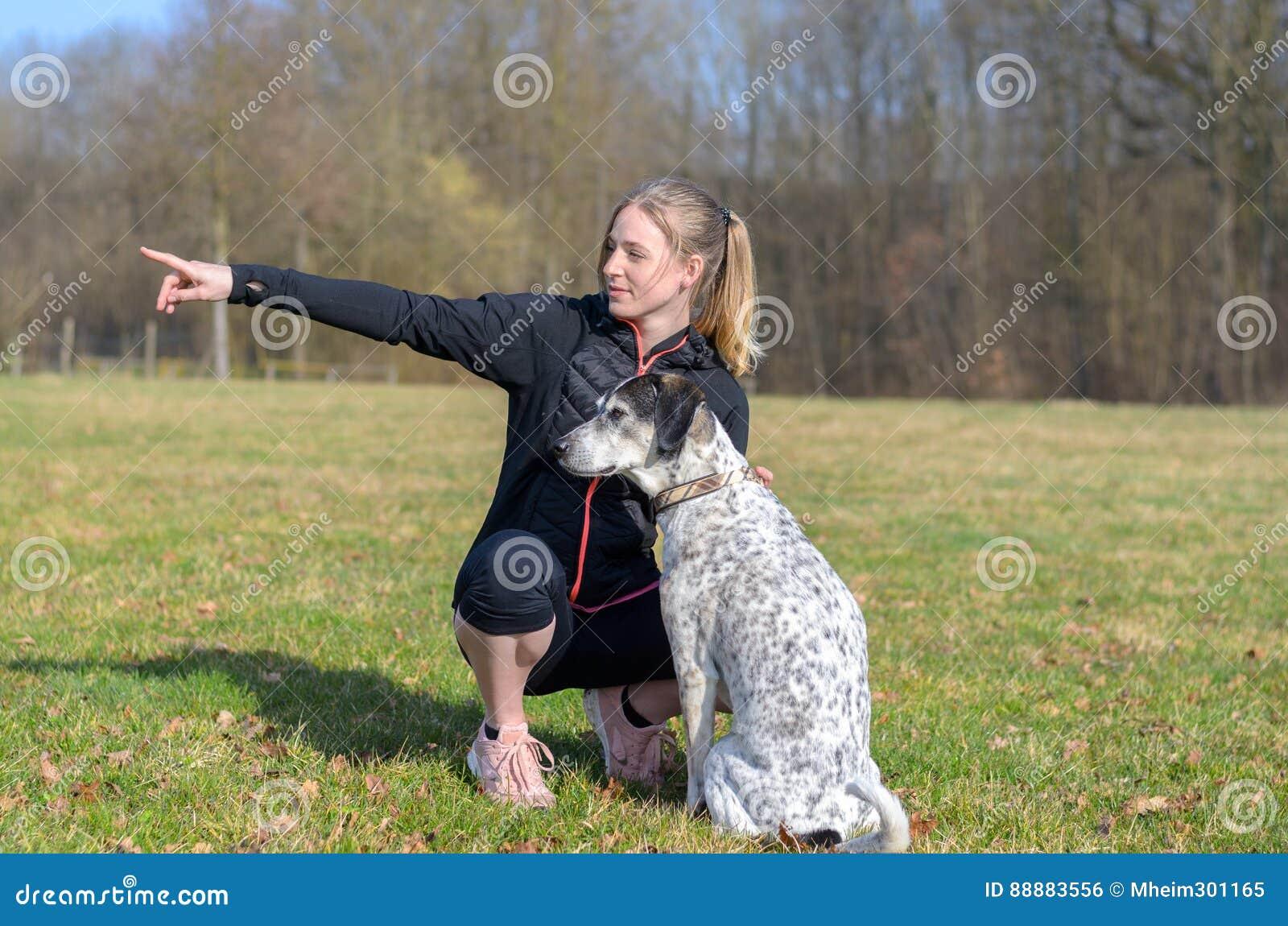 Милая молодая женщина уча ей командам собаки