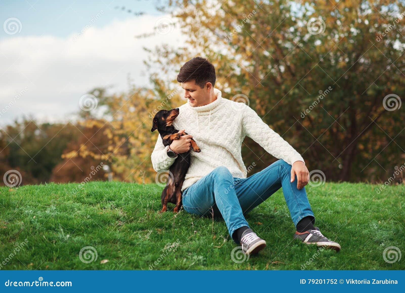 Милая собака и его человек предпринимателя молодой красивый имеют потеху в парке, животных зачатий, любимчиков, приятельство