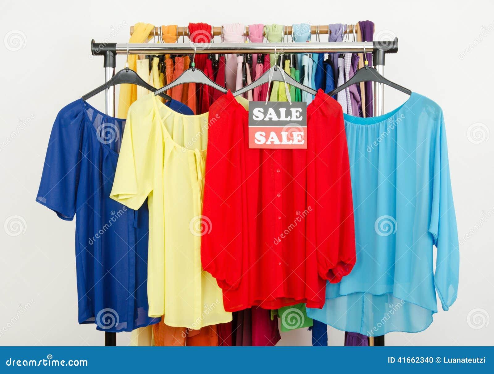 Милые красные, желтые, голубые блузки показанные на вешалках с продажей подписывают