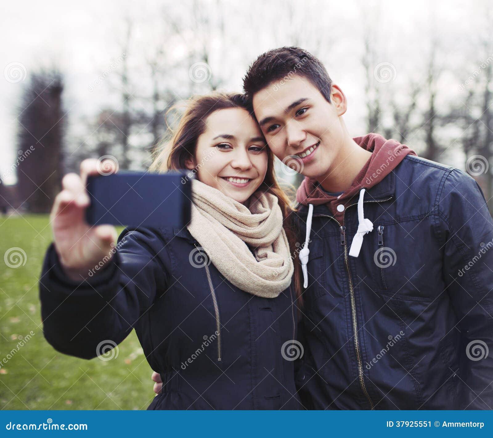 Милые молодые пары принимая автопортрет в парке
