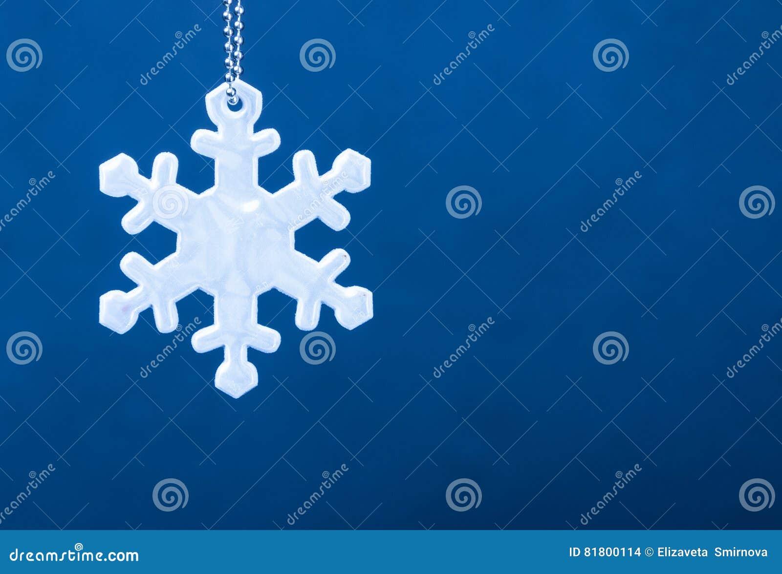 Милый белый рефлектор безопасности в форме снежинок на голубой предпосылке Необходимое оборудование к пешеходам для прогулок
