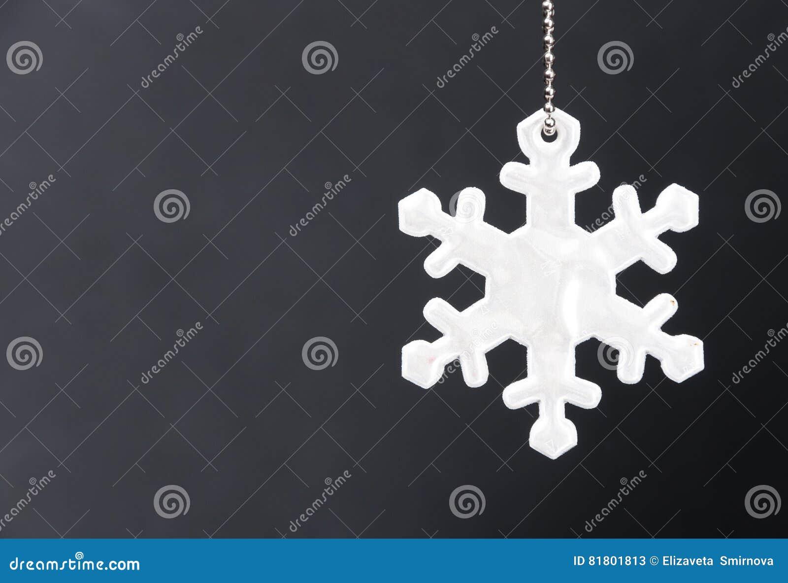 Милый белый рефлектор безопасности в форме снежинок на черной предпосылке Необходимое оборудование к пешеходам для прогулок
