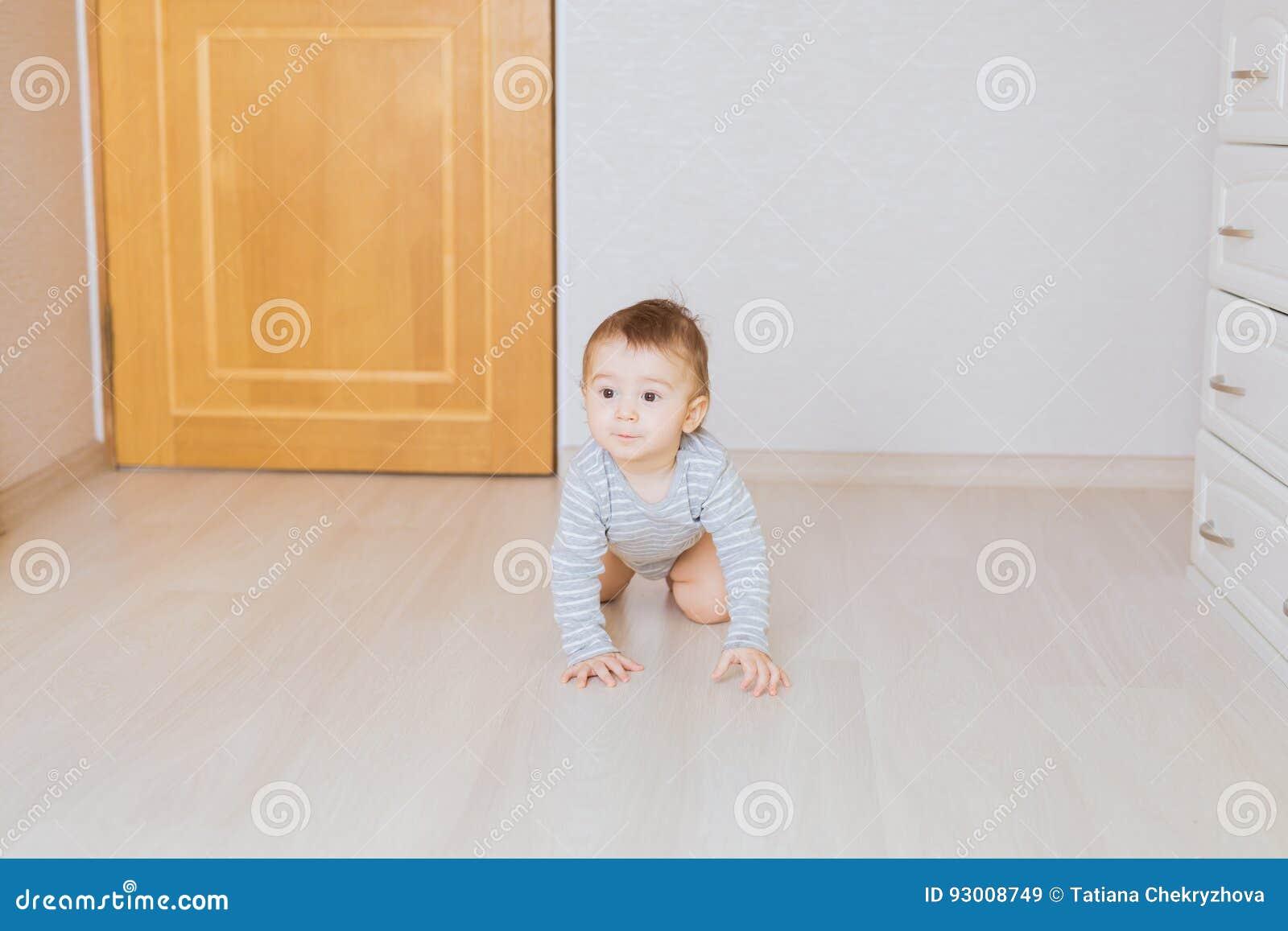 Милый вползая смешной ребёнок внутри помещения дома