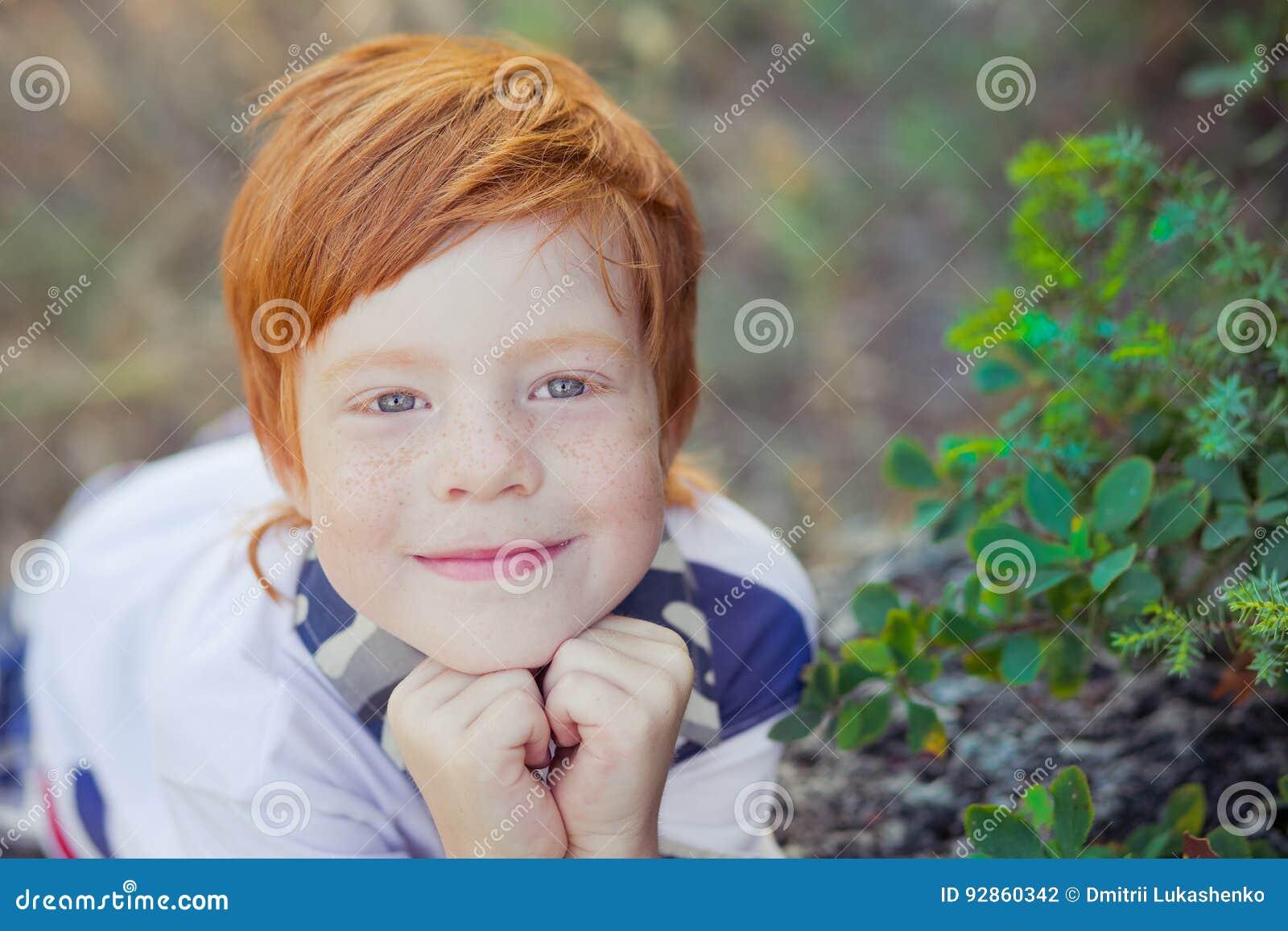 Милый красный мальчик волос усмехаясь к камере и положению в лесе с лошадью