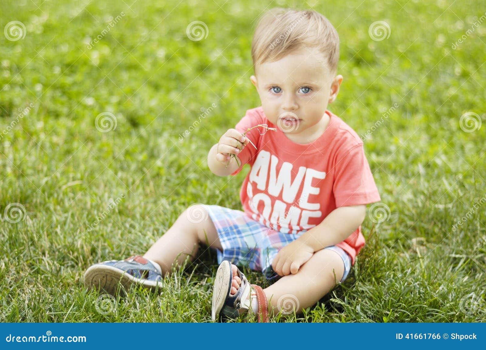 Милый малый мальчик на траве
