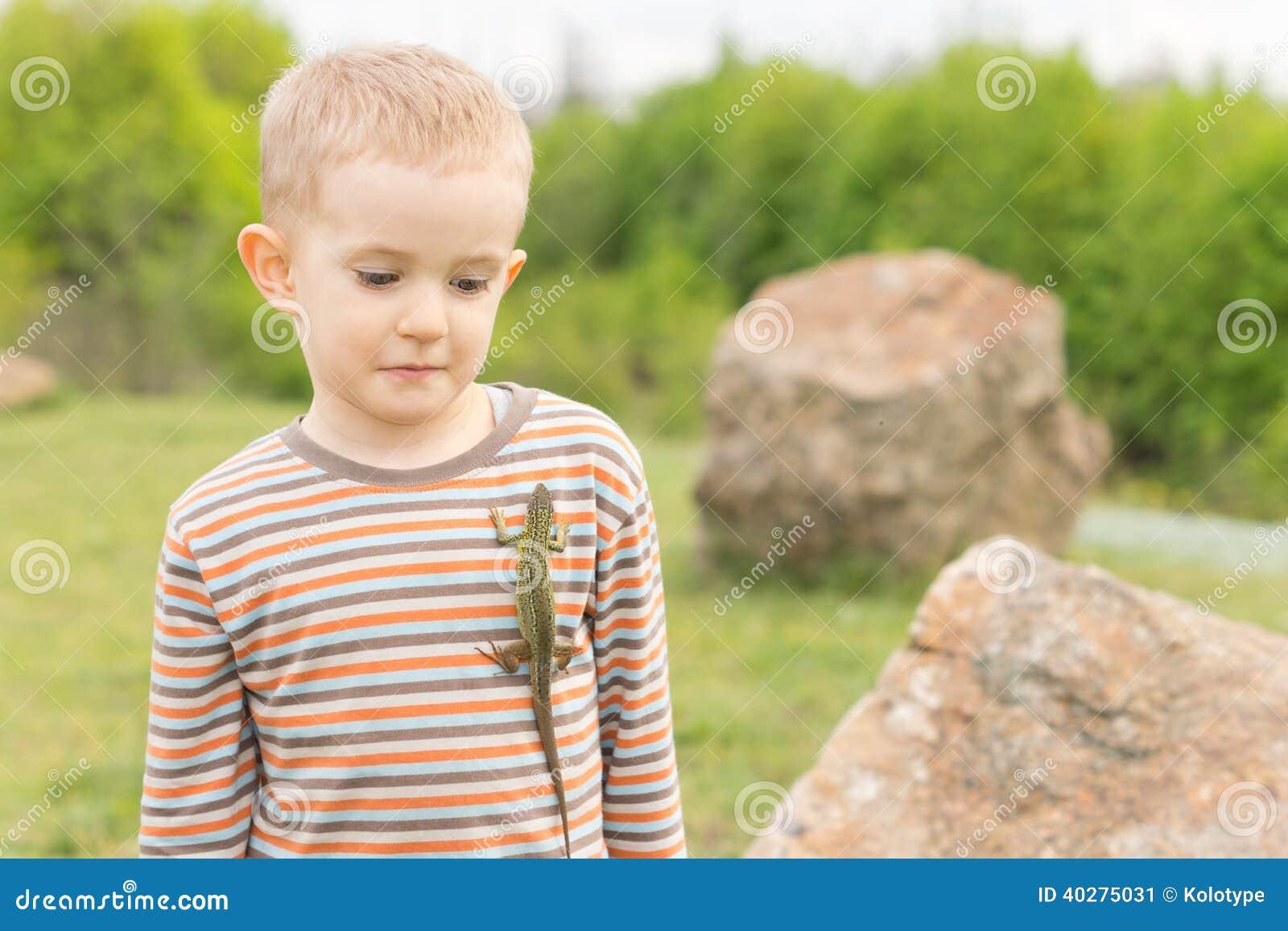 Милый мальчик с ящерицей на его комоде
