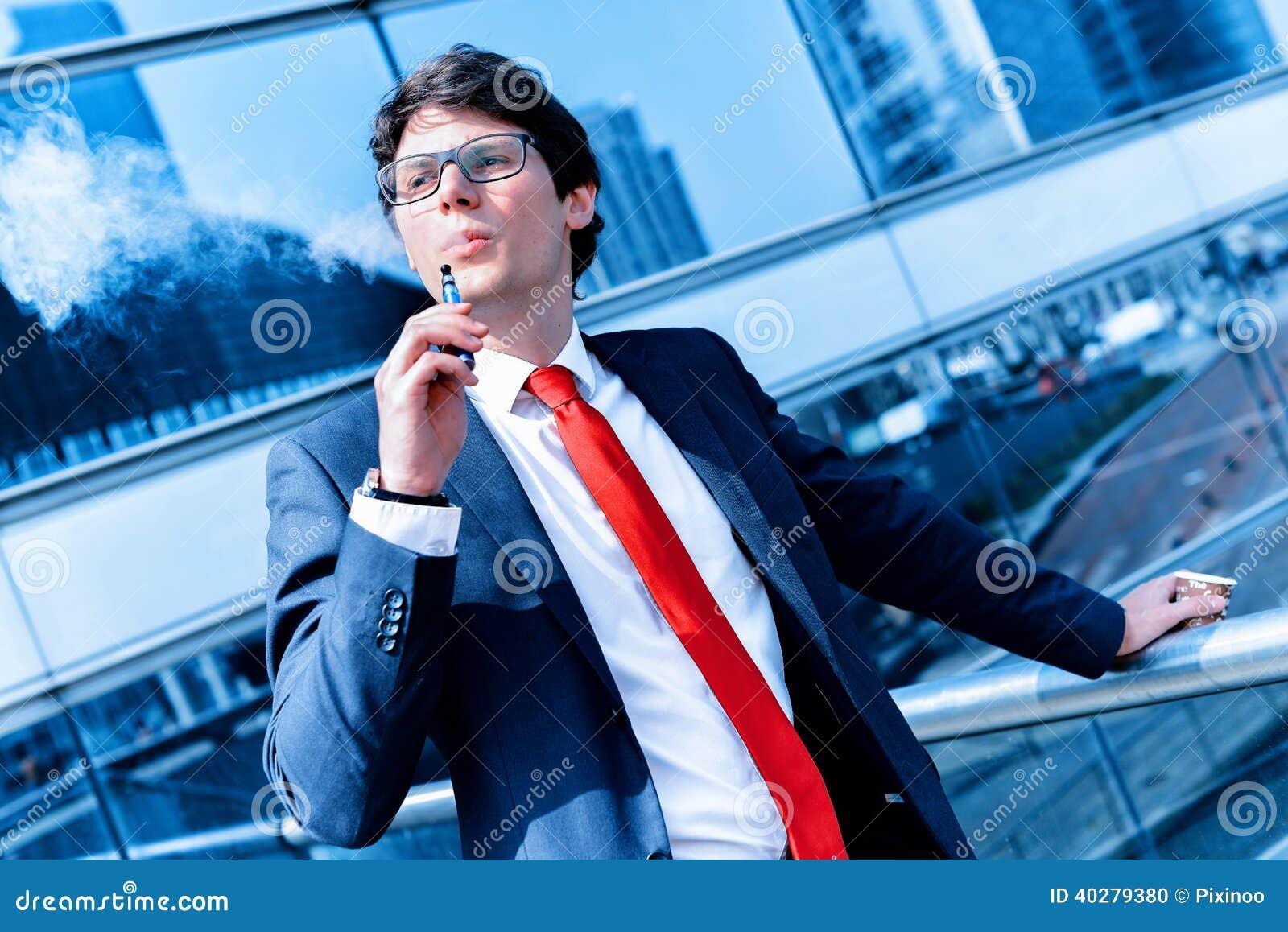 Милый молодой взрослый человек вдыхая от электронной сигареты