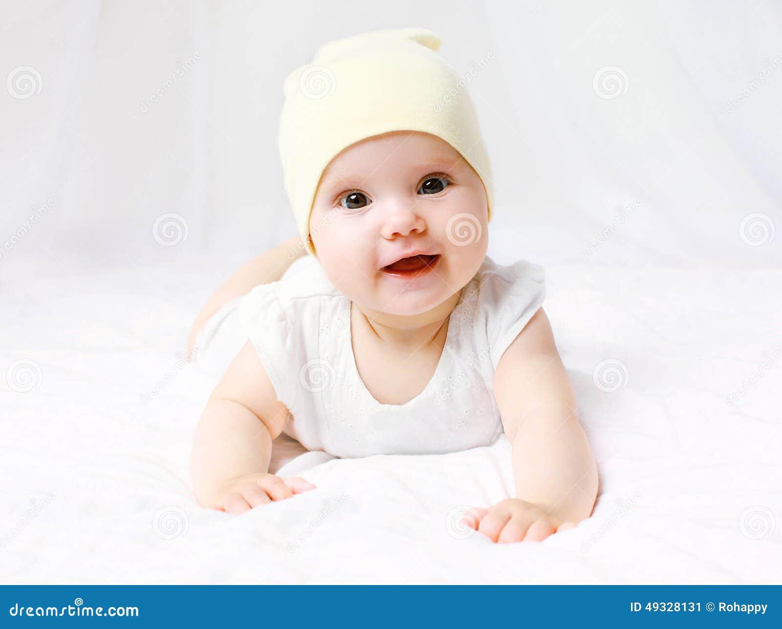 Милый младенец в шляпе на кровати