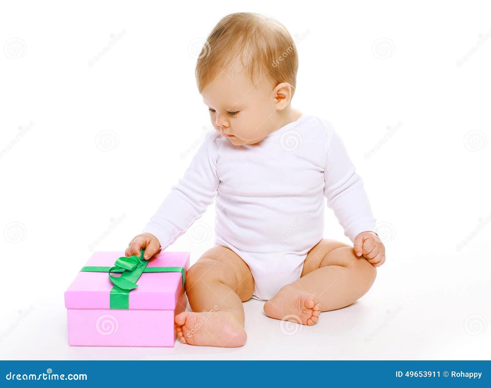 Милый младенец сидя с подарочной коробкой