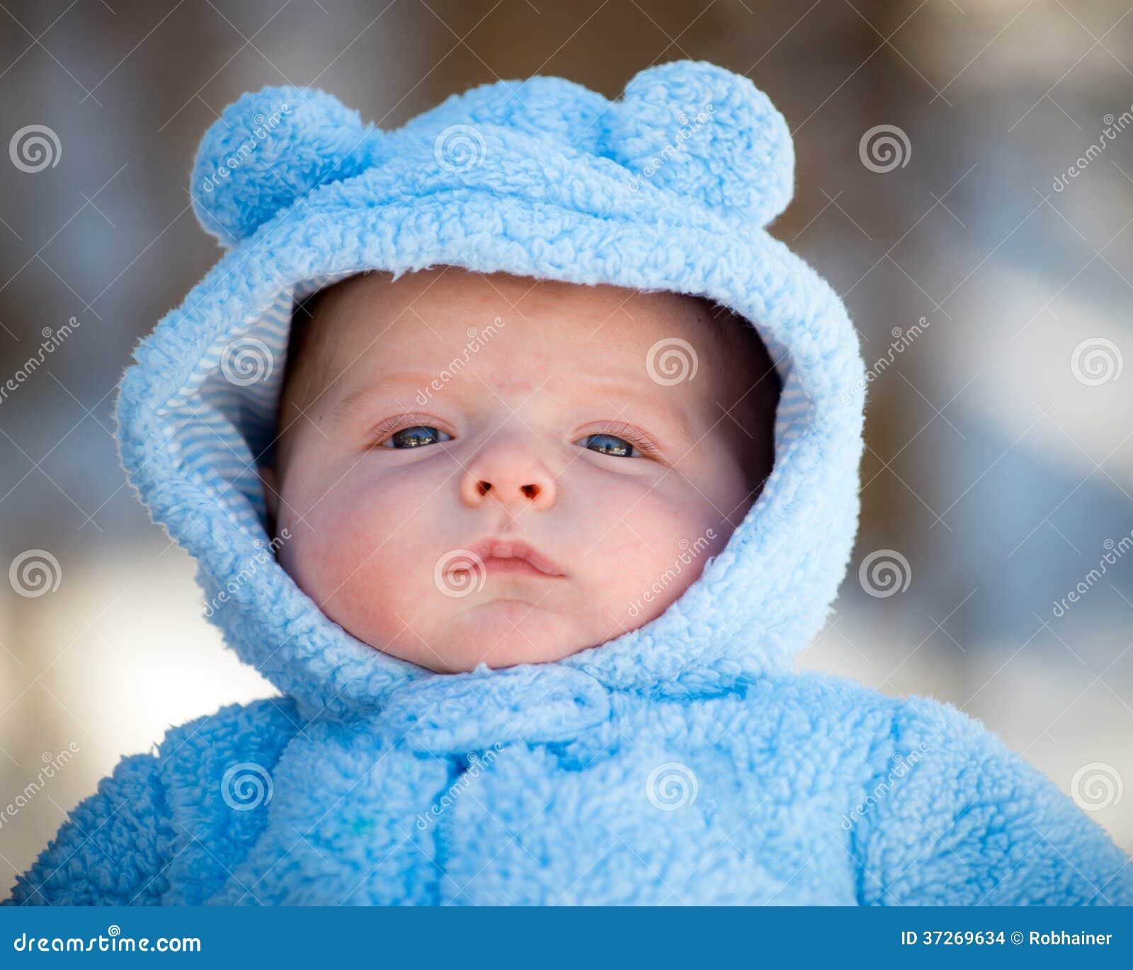 Милый младенческий ребёнок нося пушистый костюм снега