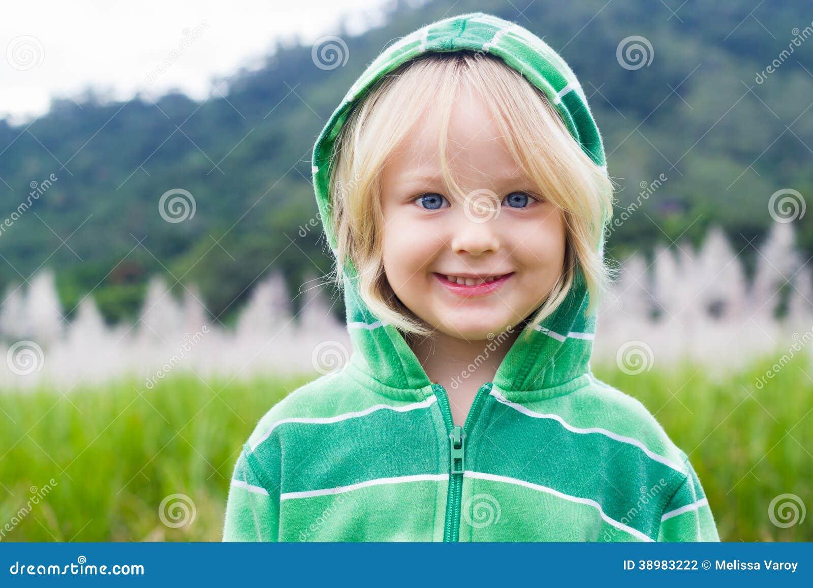 Милый, счастливый ребенок в hoodie перед полем