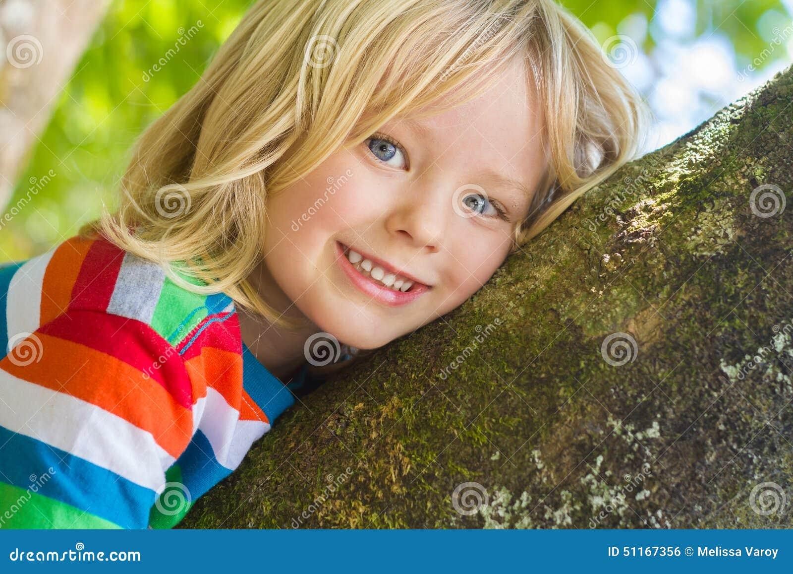 Милый счастливый, усмехаясь ребенок ослабляя outdoors в дереве