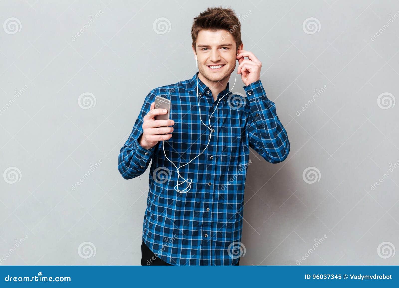 Милый человек смотря камеру пока слушая музыка