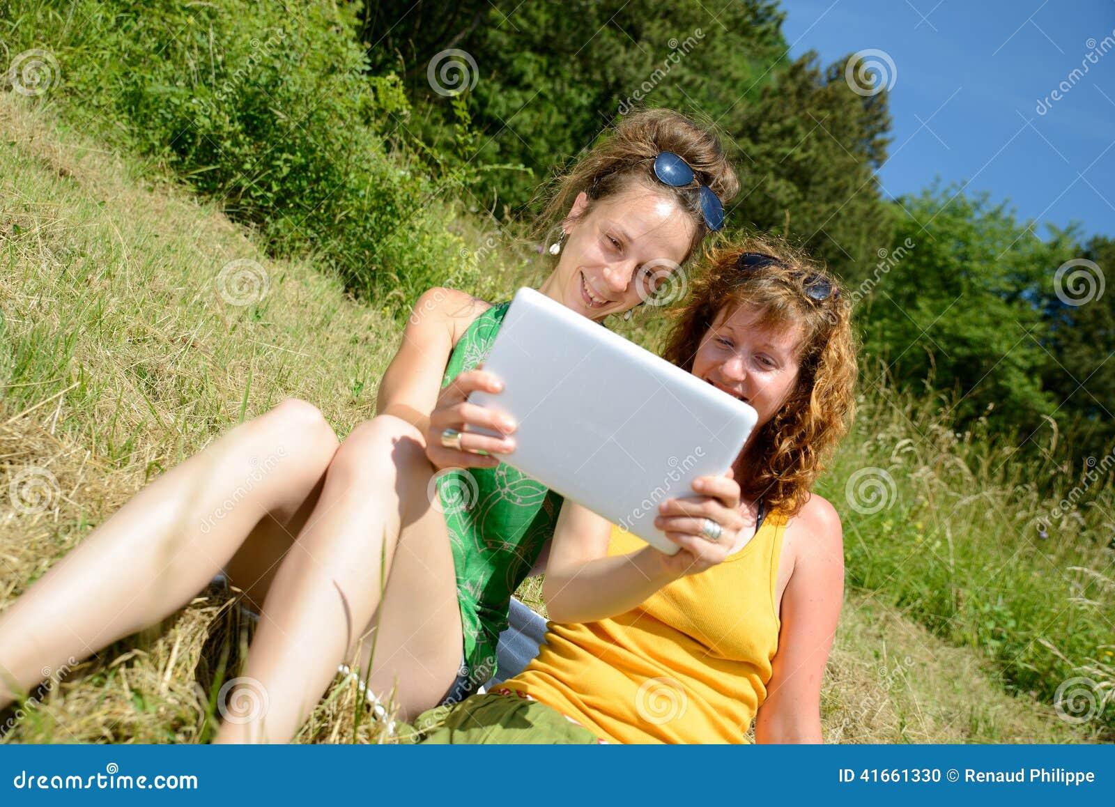 2 милых девушки на траве с цифровой таблеткой