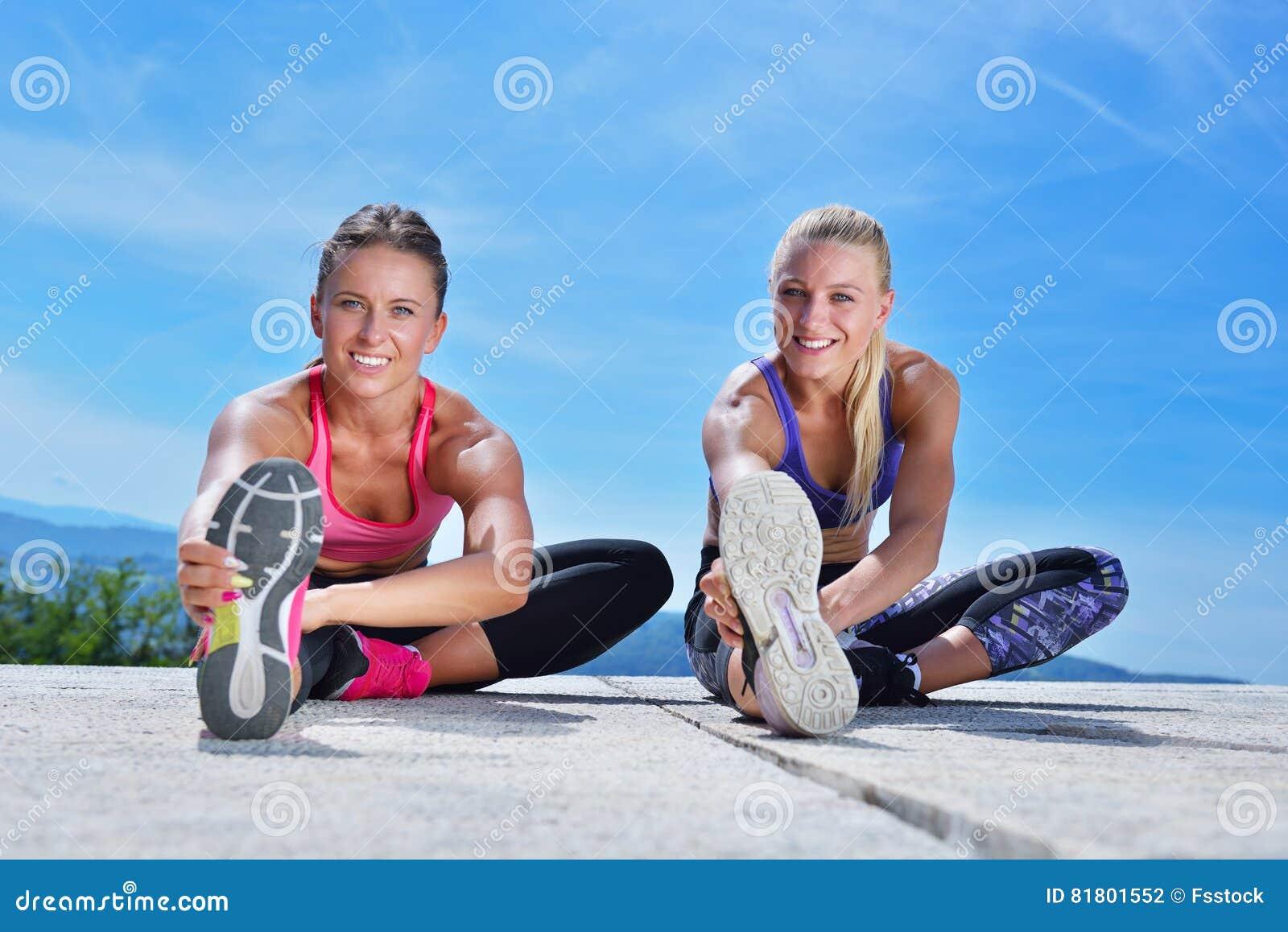 2 милых женщины протягивая в парке перед начинать встречу разминки