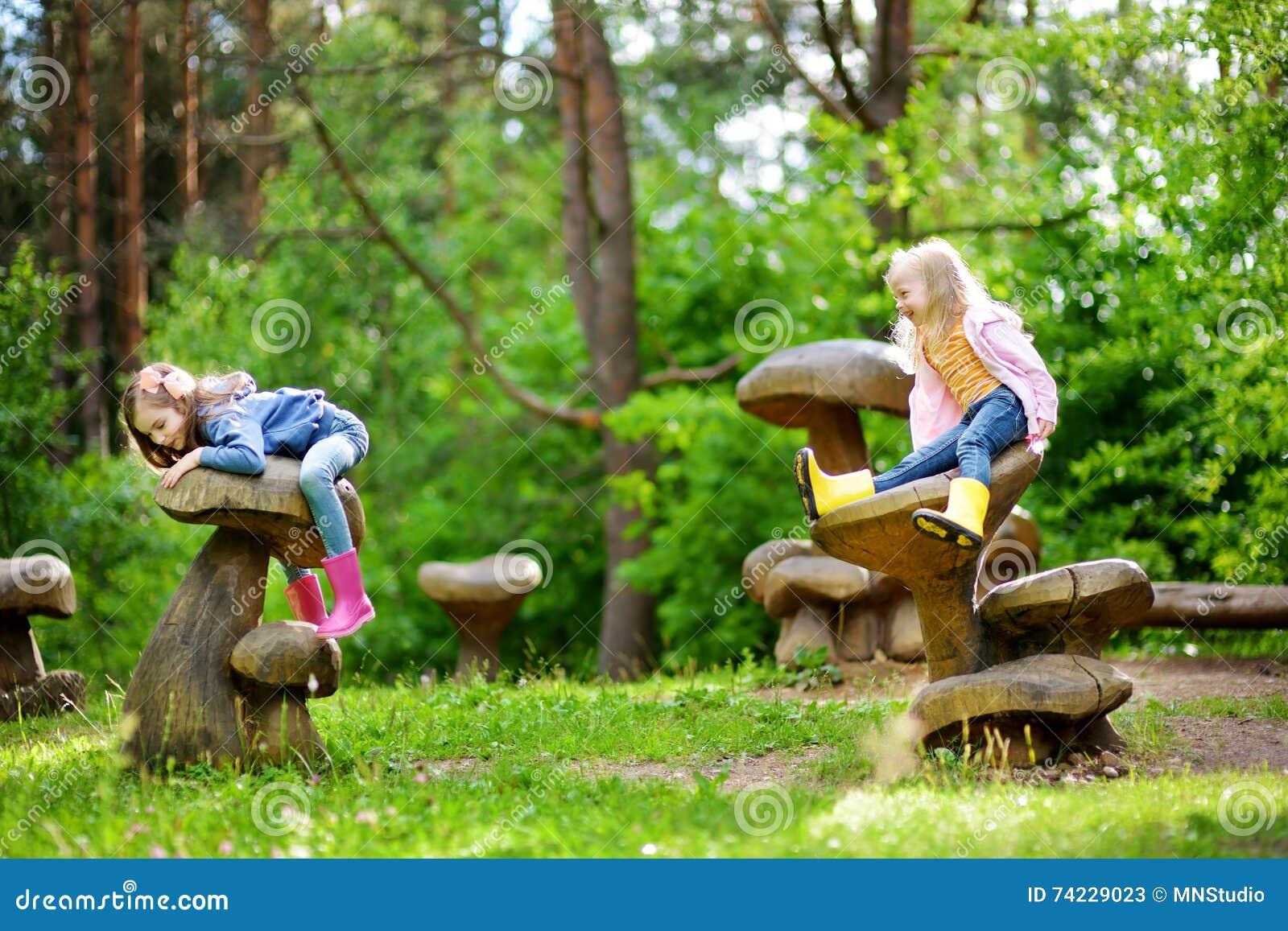 2 милых маленьких сестры имея потеху на гигантских деревянных грибах