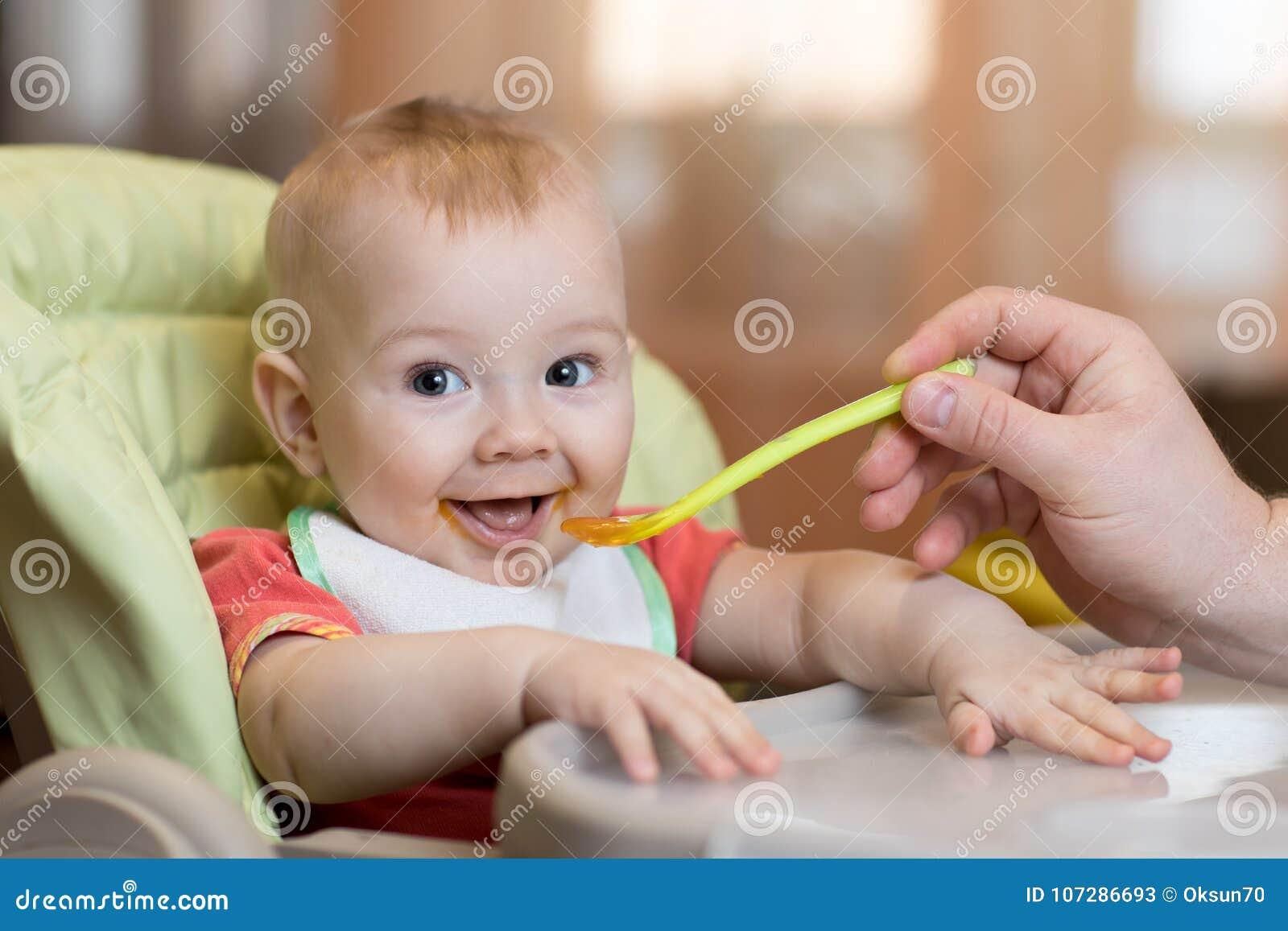 Младенец есть еду с помощью отца
