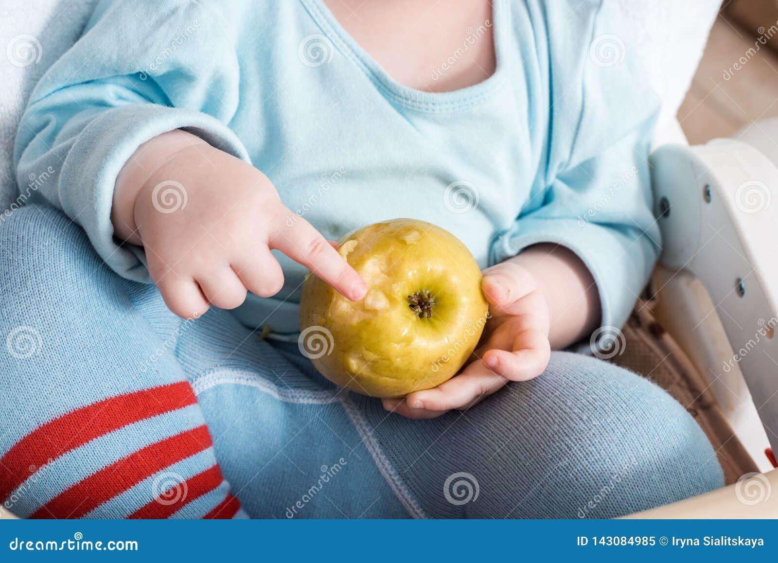 Младенец есть плод Яблоко мальчика сдерживая сидя в белом высоком стуле в солнечной кухне с окном и раковиной m