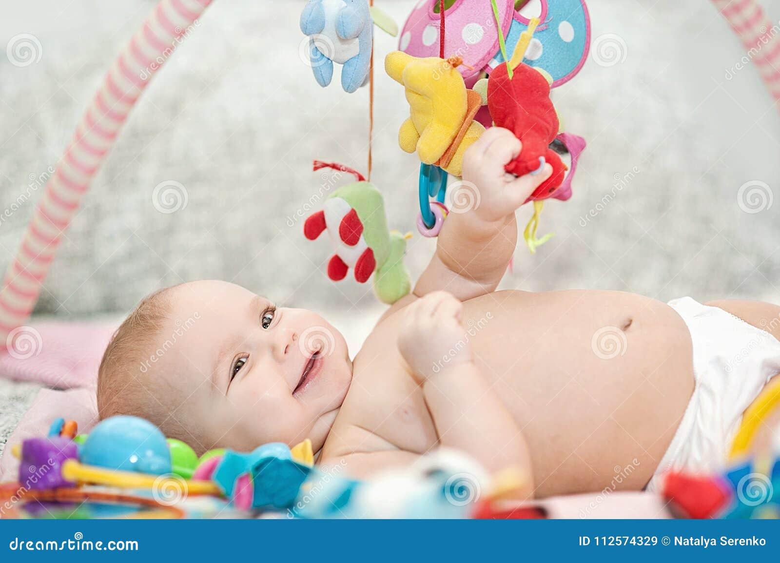 Младенец лежа на превращаясь половике играть в черни воспитательные игрушки Сладостный ребенок вползая и играя с игрушками на ков