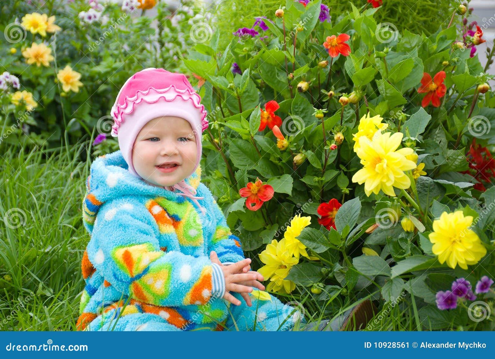 младенец рассматривает цветок