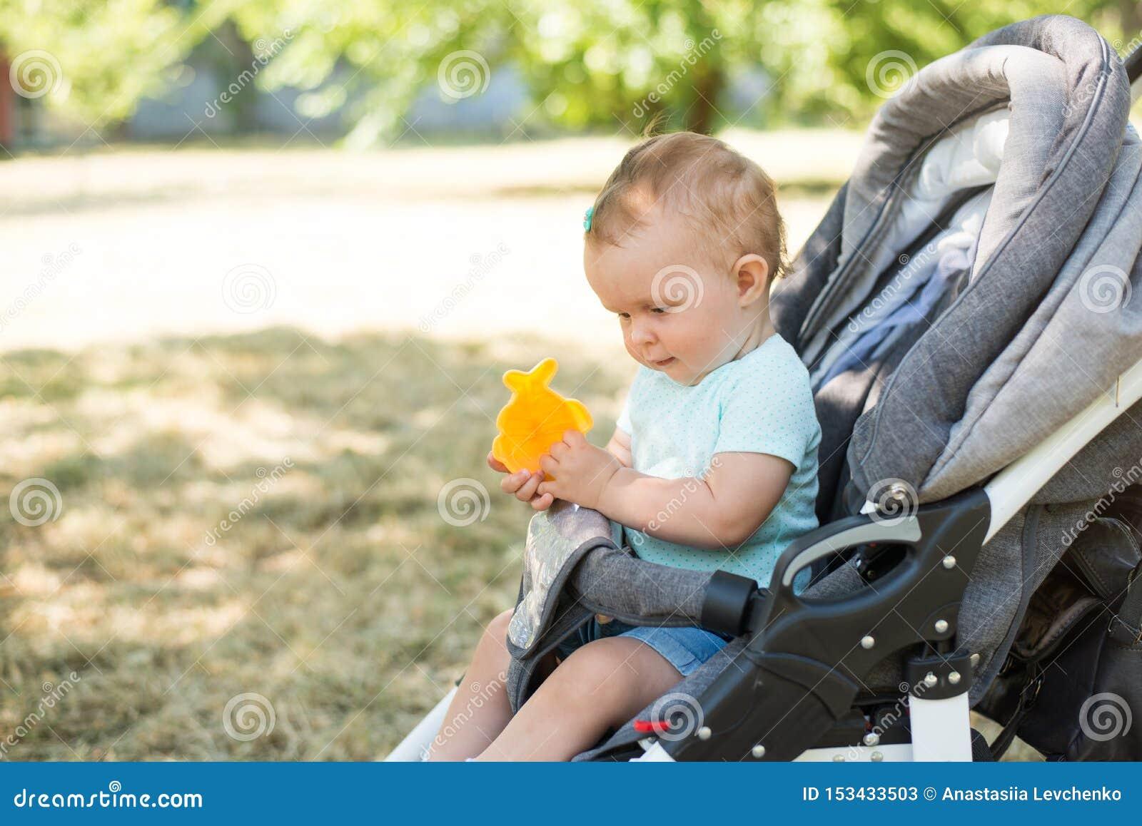 Младенец сидя в прогулочной коляске, предпосылке природы с космосом экземпляра o