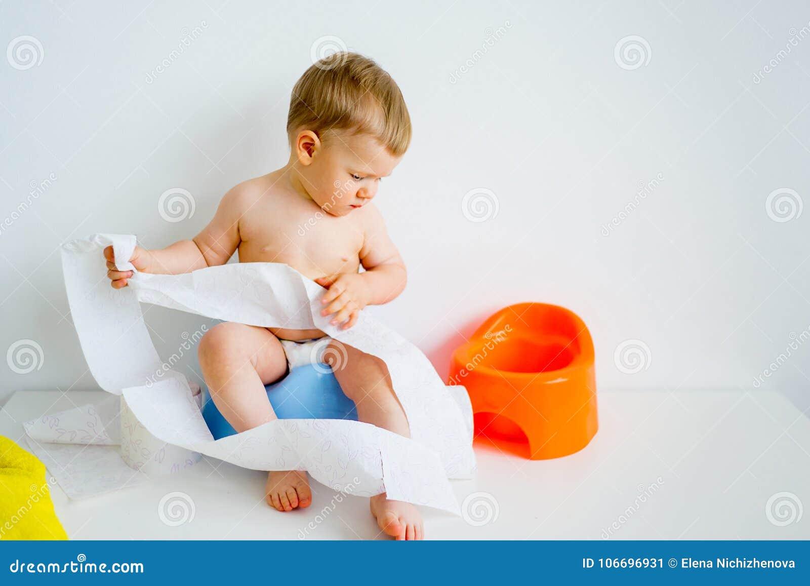 Младенец сидя на горшочке