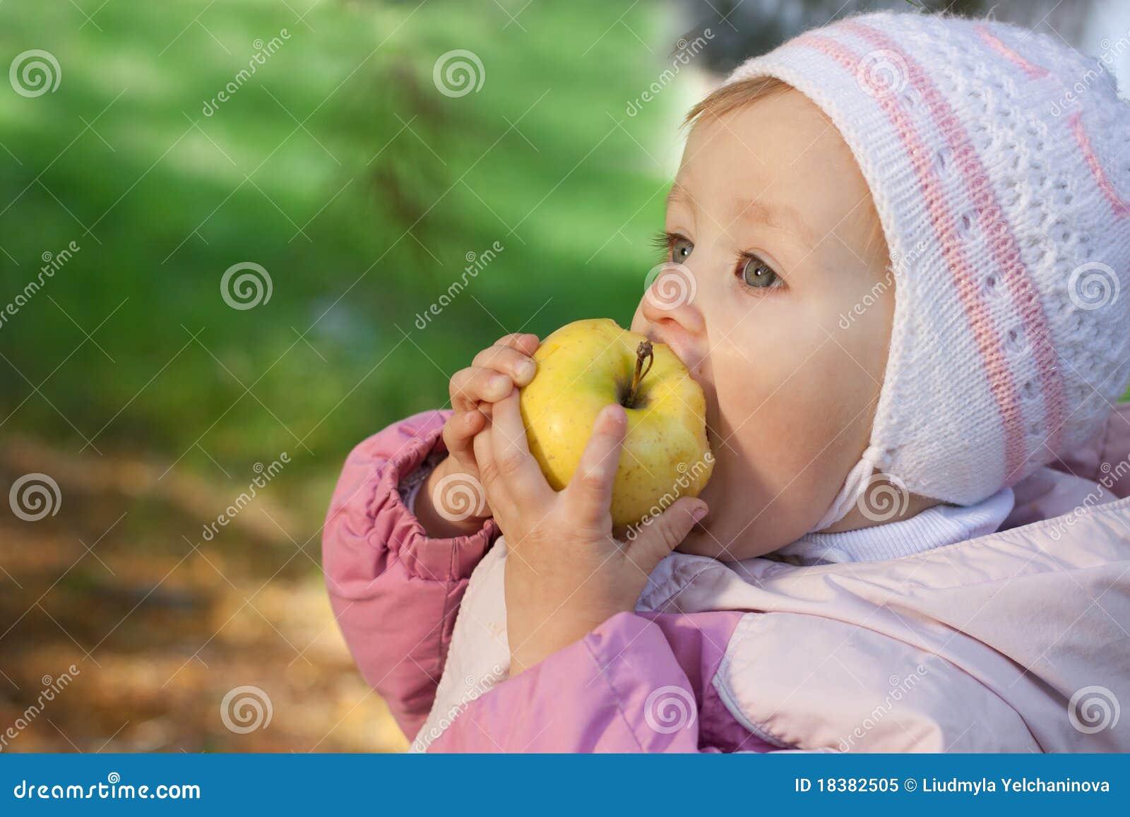 младенец яблока есть желтых детенышей