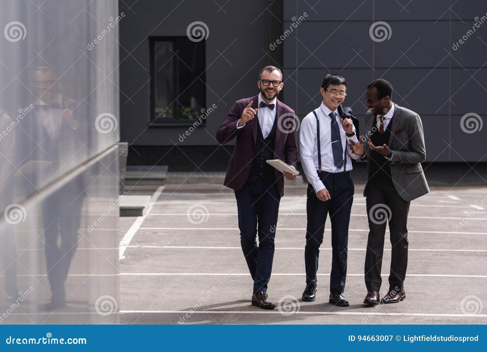 Многокультурная команда дела идя на улицу около современного офисного здания