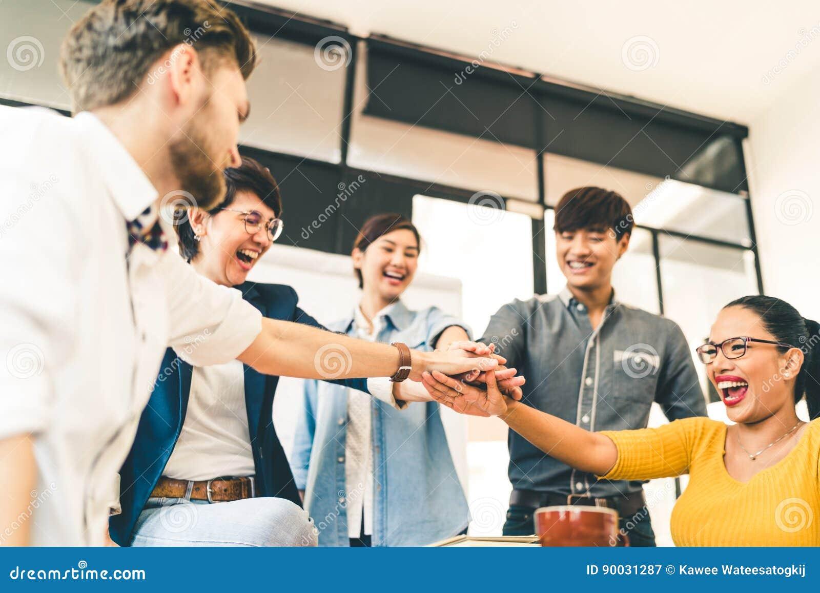 Многонациональная разнообразная группа в составе счастливые коллеги соединяет руки совместно Творческая команда, вскользь сотрудн