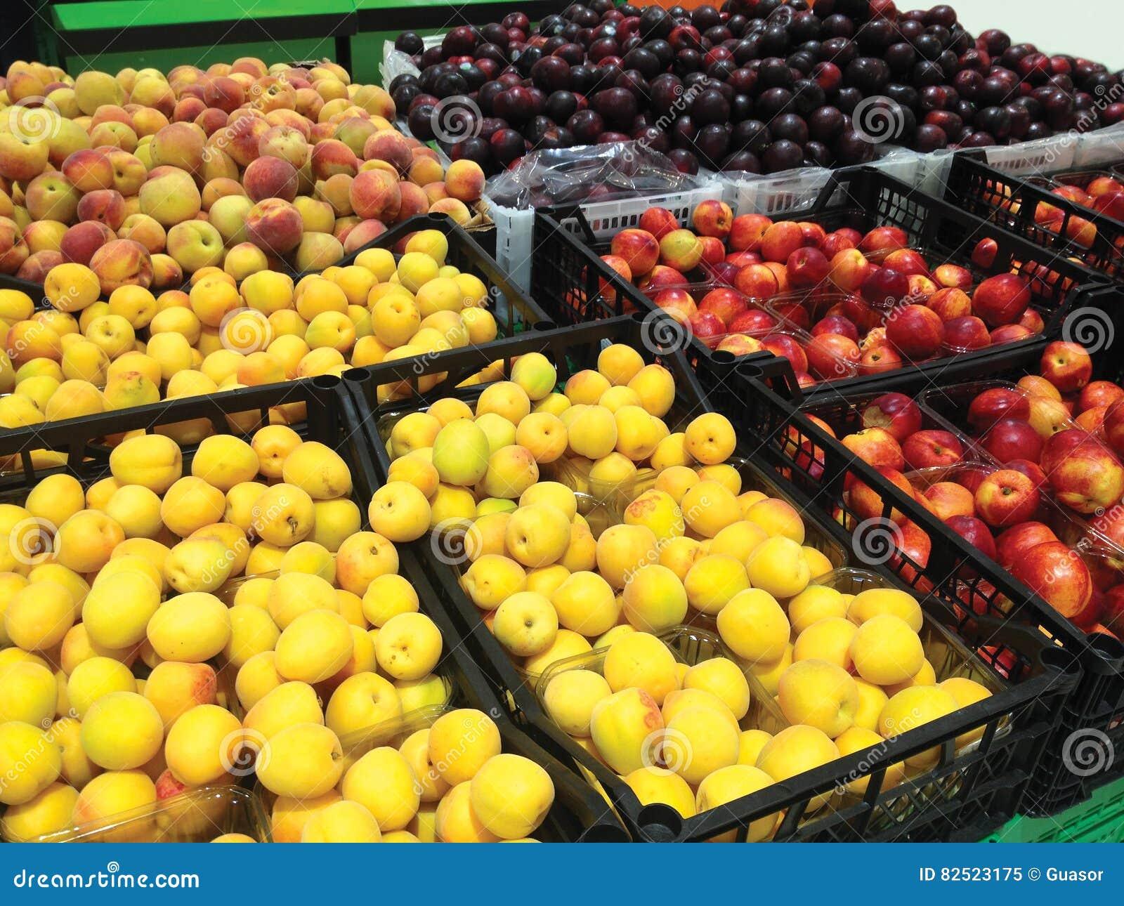 Много абрикосы, персики, нектарины и слив плодоовощей лежа в супермаркете коробок