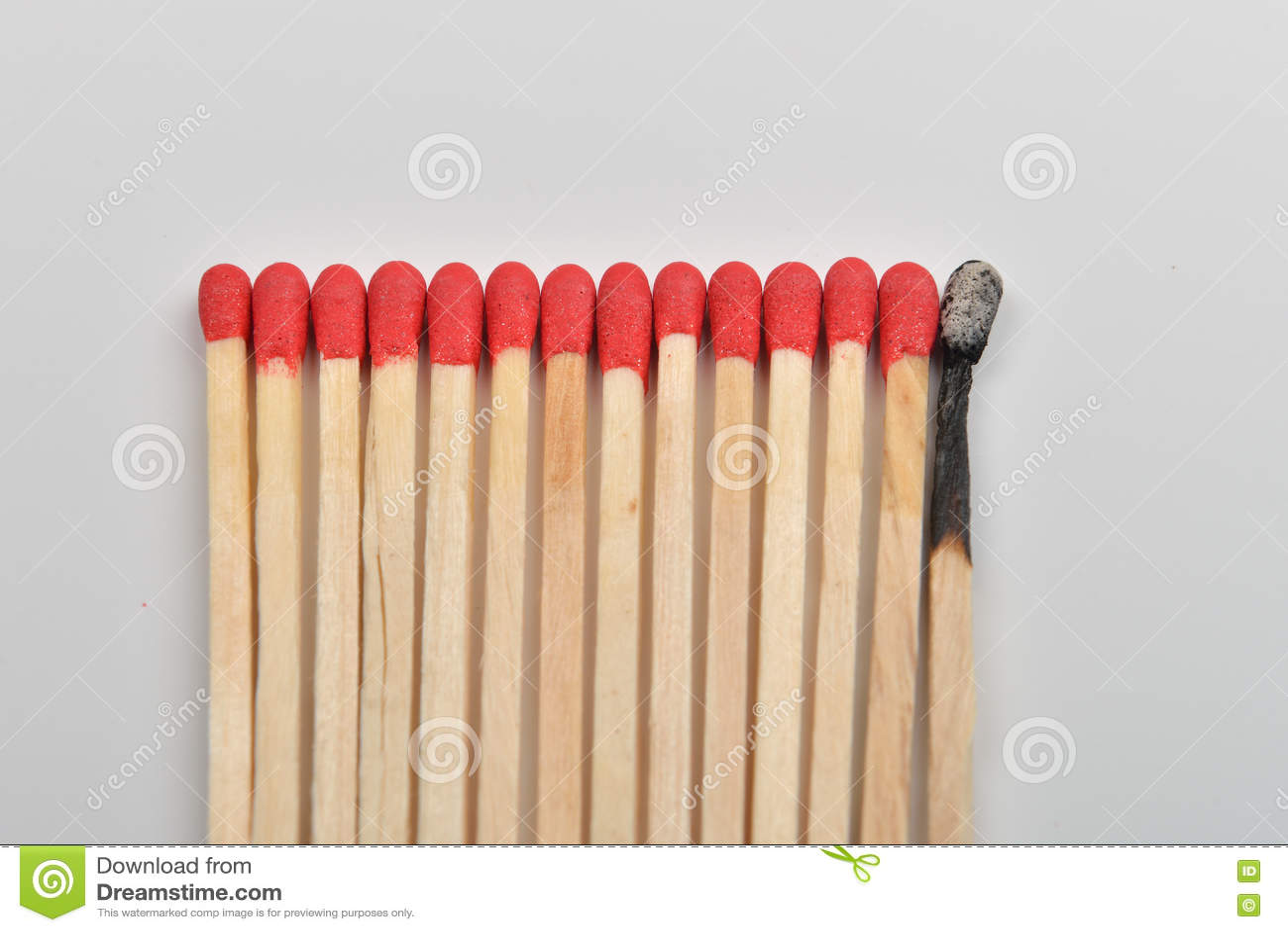 Много красных головных спичек и сгорели одно, который положенными прямо в линию на whi