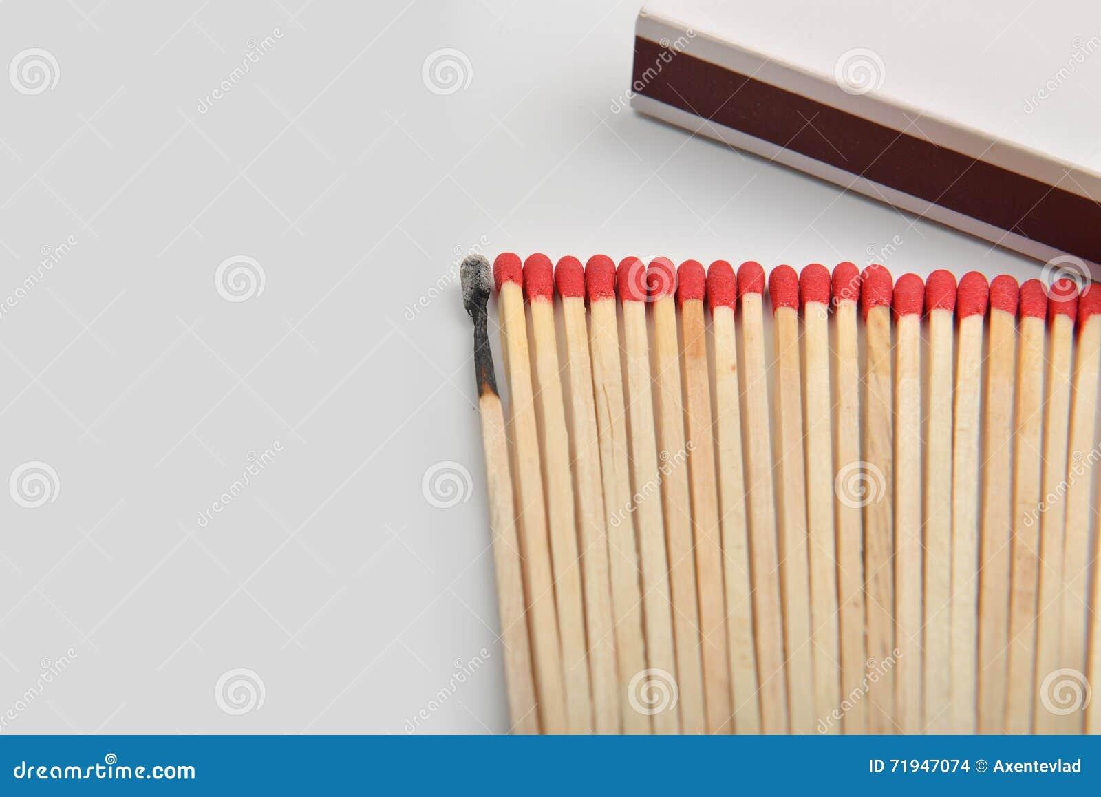 Много красных головных спичек и сгорели одно, который положенными прямо в линию около a