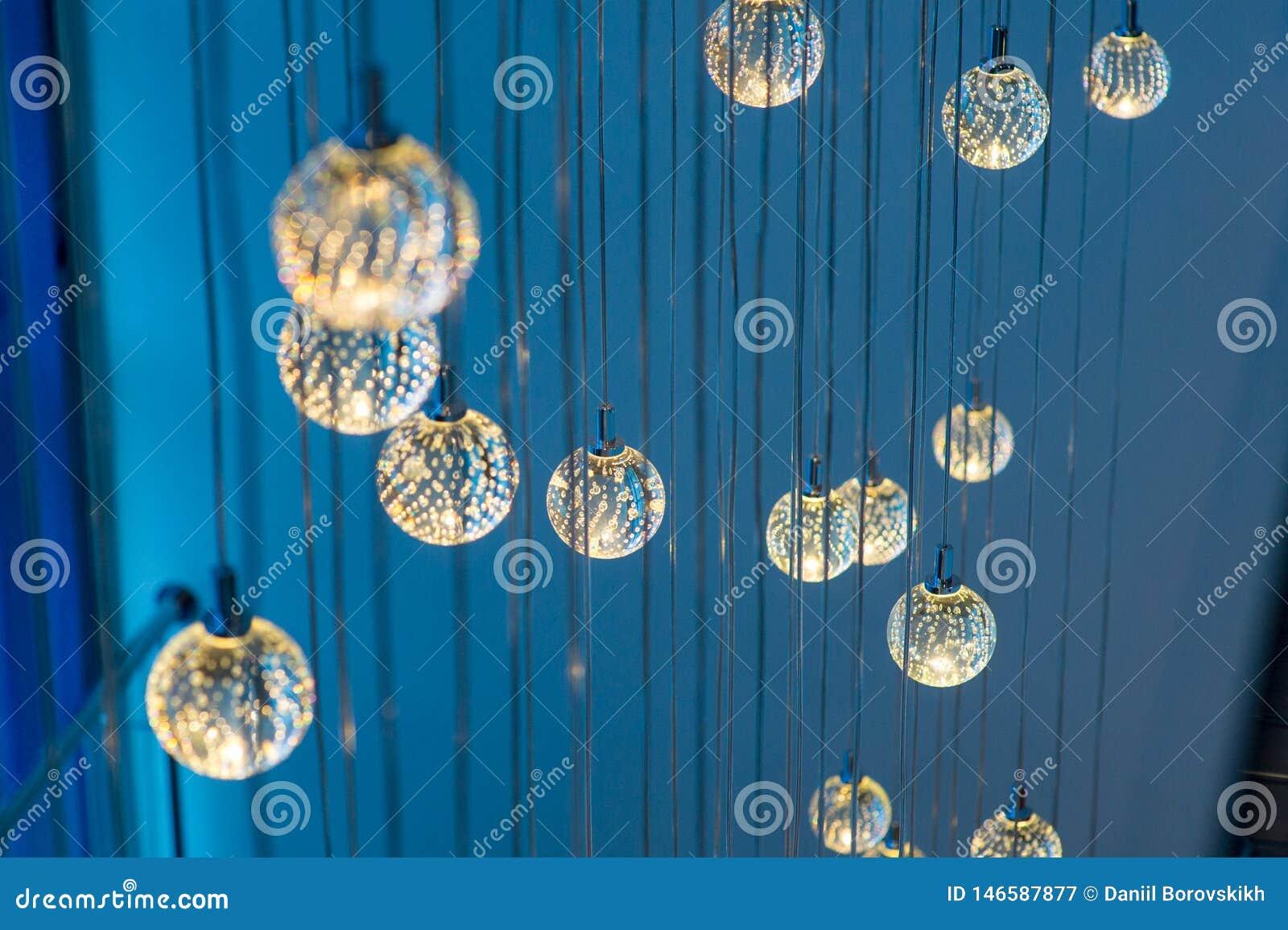 Много круглых накаляя ламп вися на голубой предпосылке