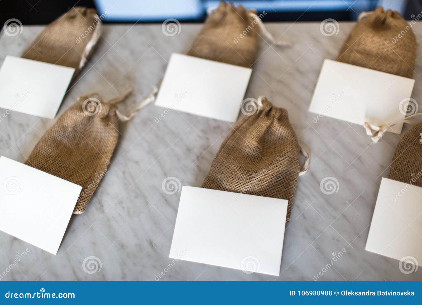 Много малых коричневых сумок ткани и белых карточек