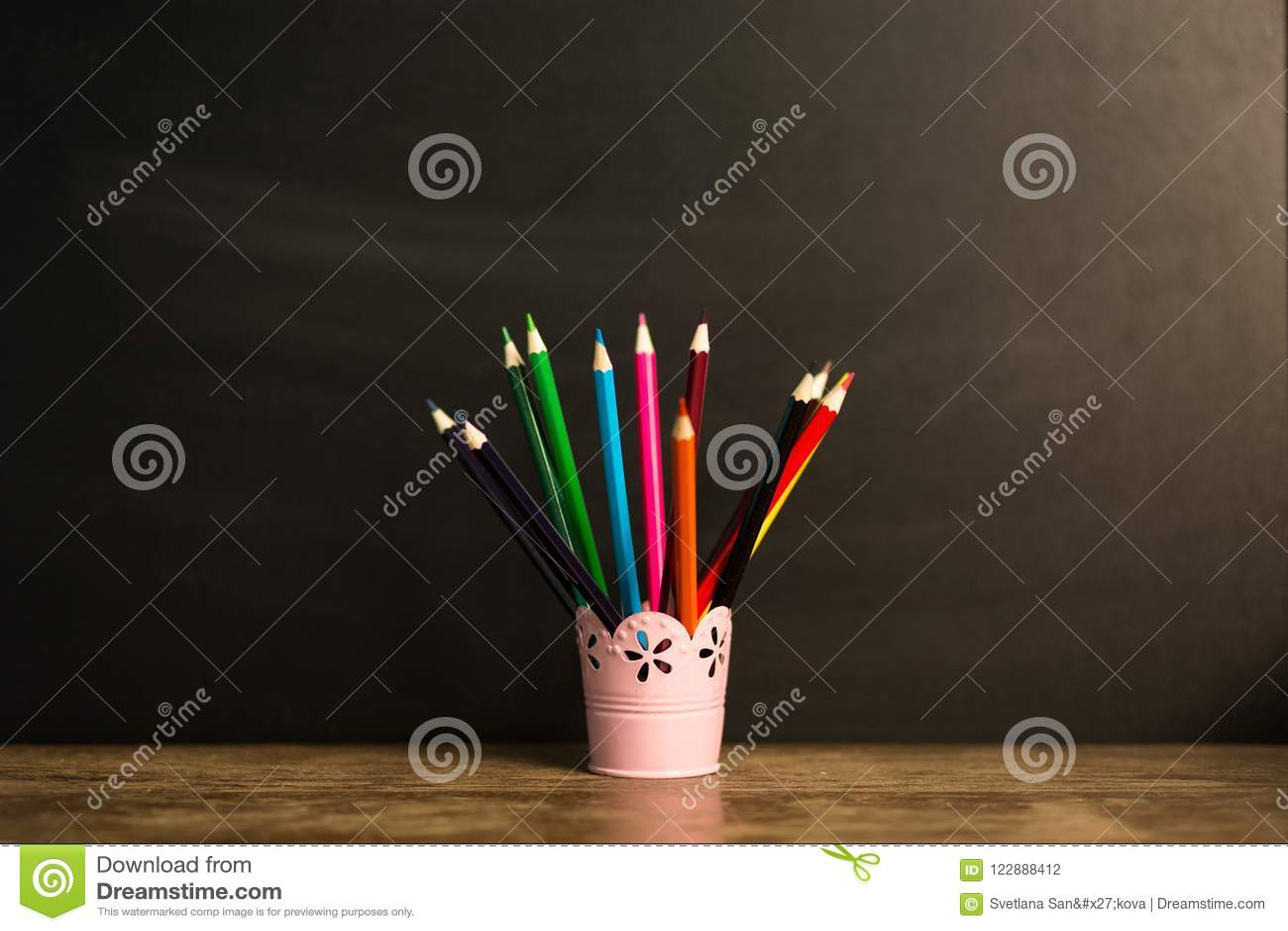 Много пестротканых карандашей в стекле на деревянном столе с черной предпосылкой задняя школа принципиальной схемы к