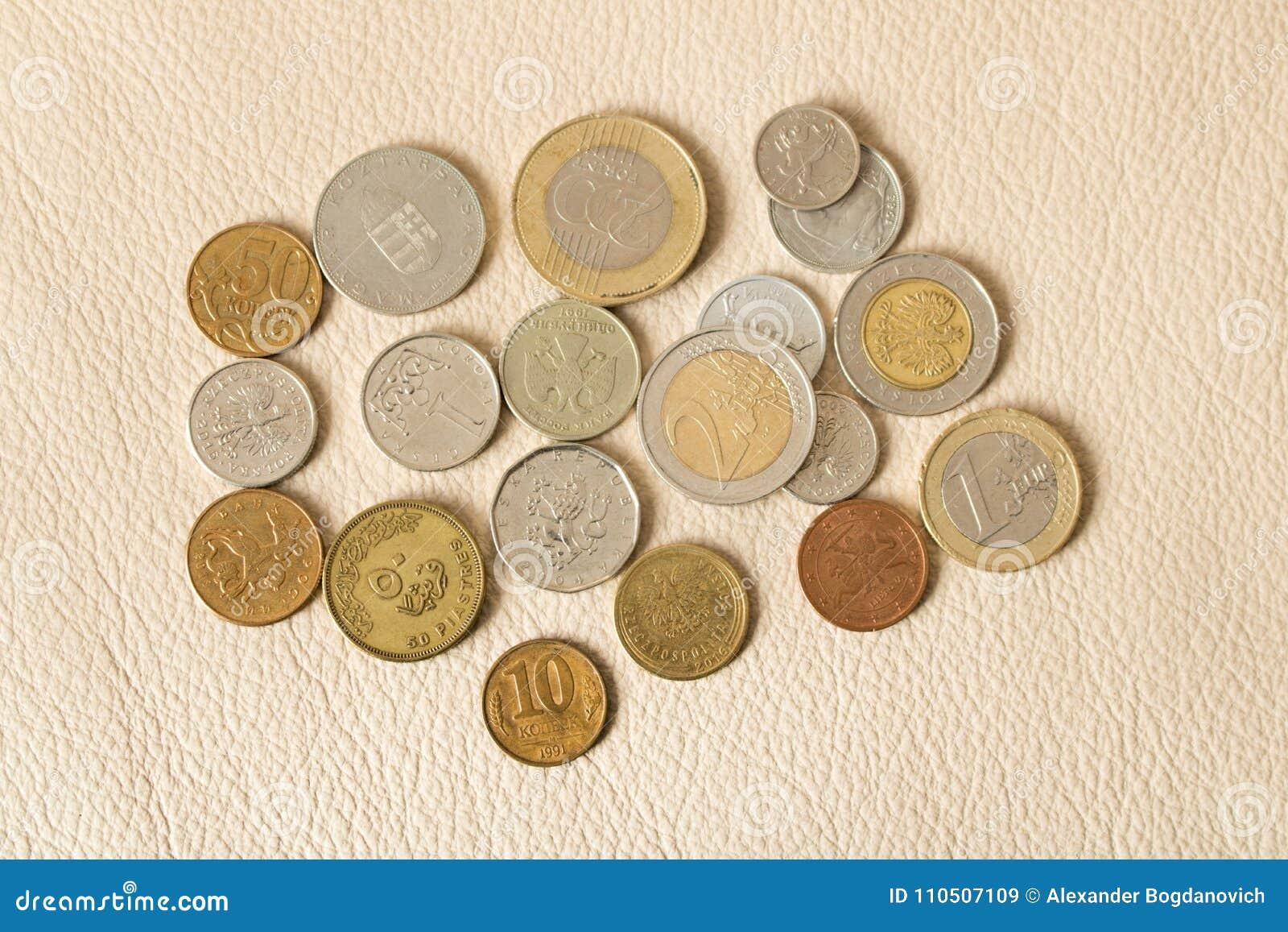 Много разбросанные монетки на кожаной предпосылке