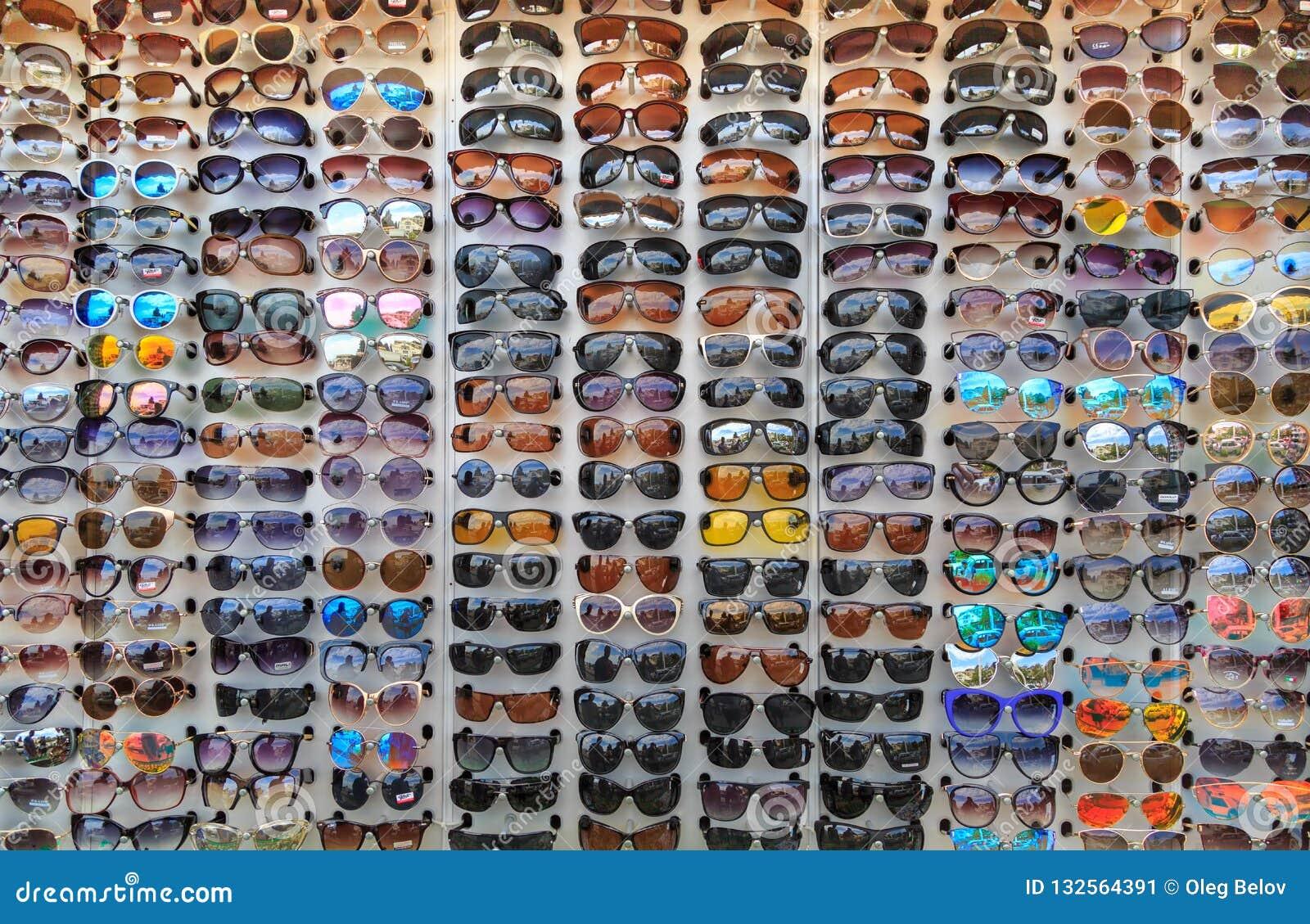 Много различных солнечных очков на внешней витрине магазина как предпосылка или фон