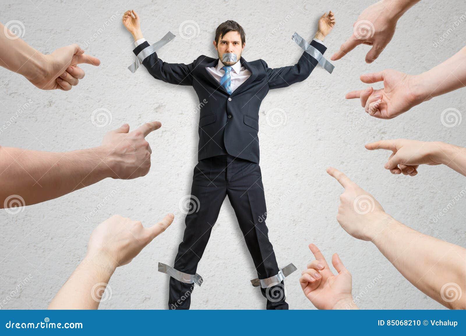 Много рук обвиняют работника который связан тесьмой к стене